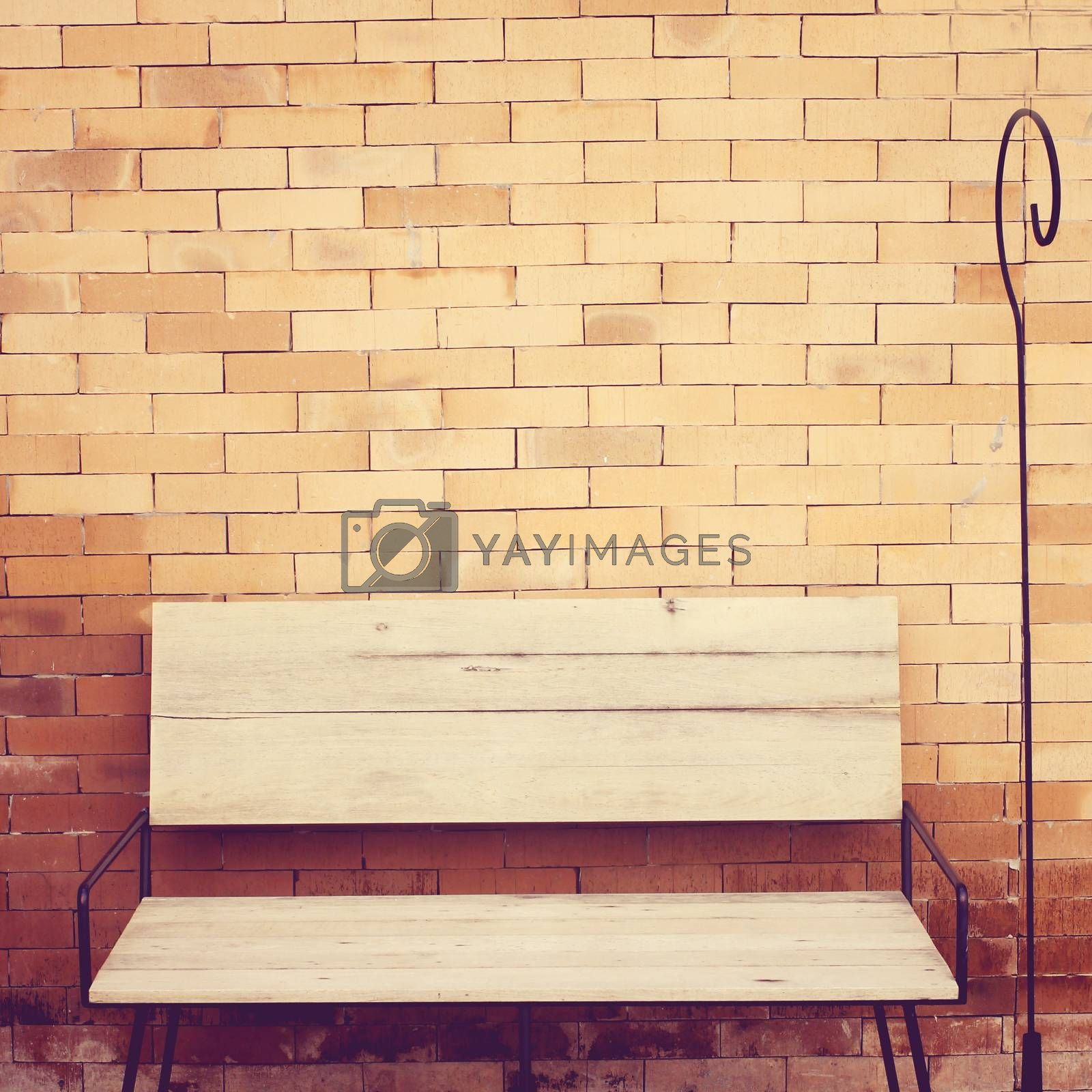 Outdoor wooden chair on brick wall, retro filter effect