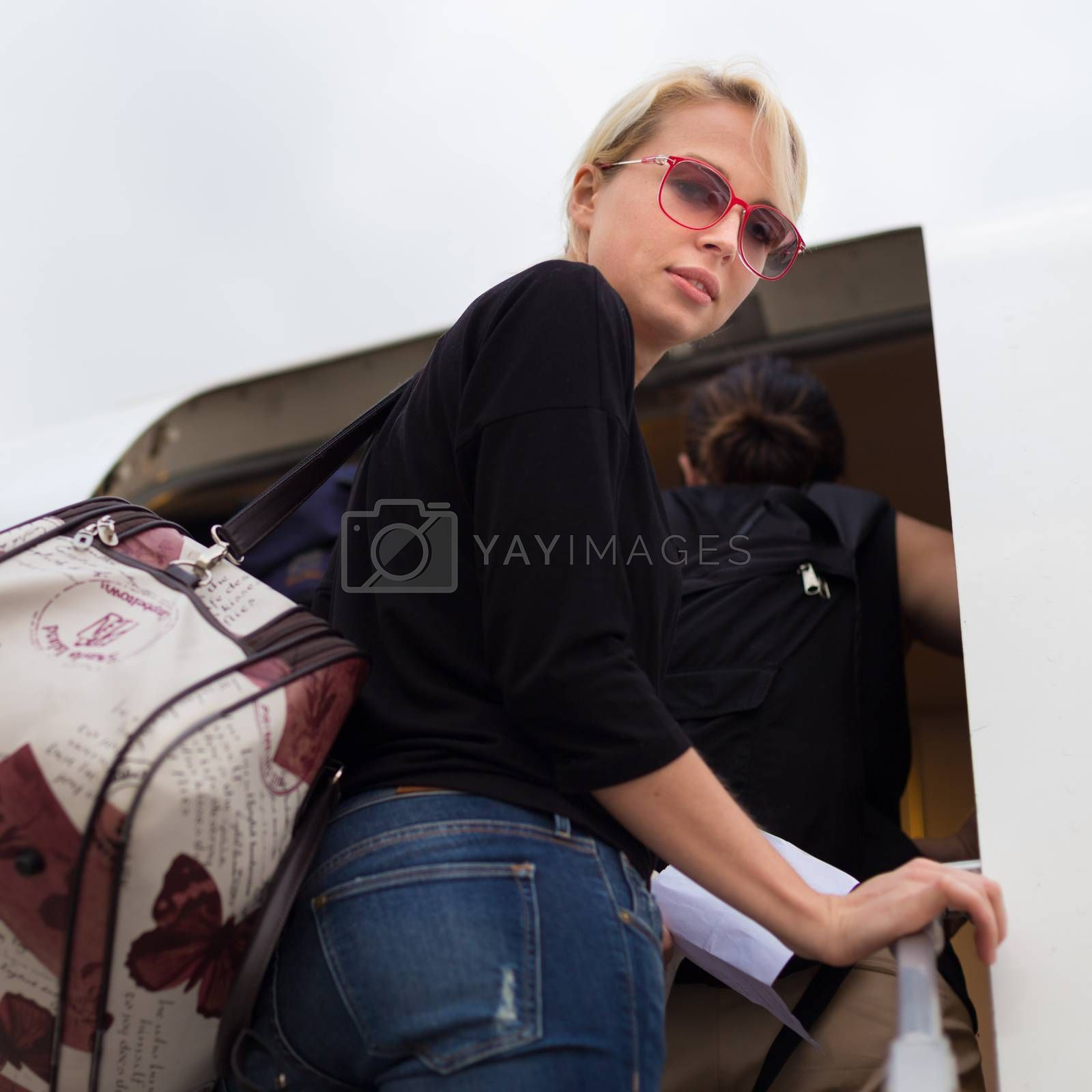 Woman holding carry on luggage queuing to board the commercial airplane.