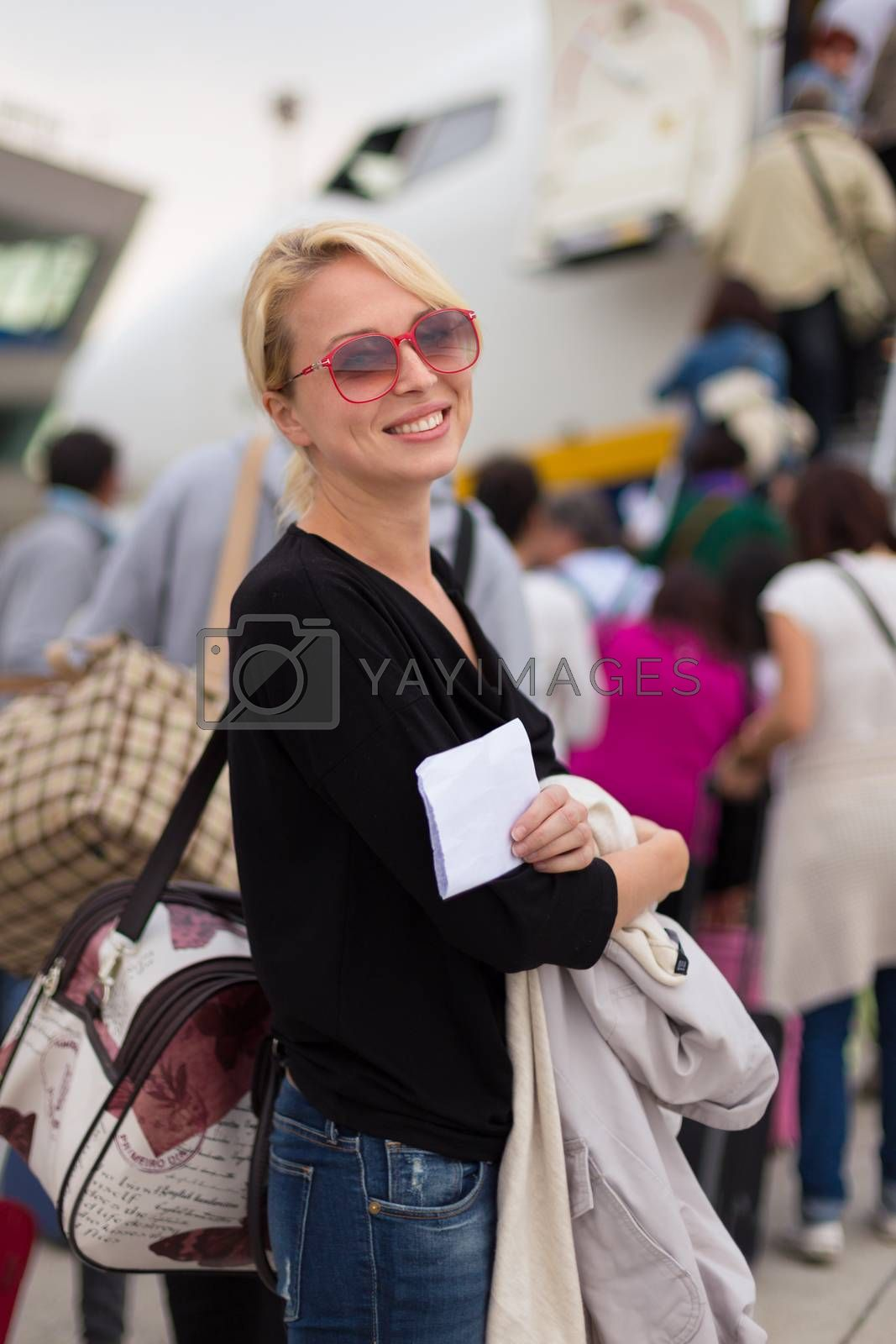 Joyful woman holding carry on luggage queuing to board the commercial airplane.