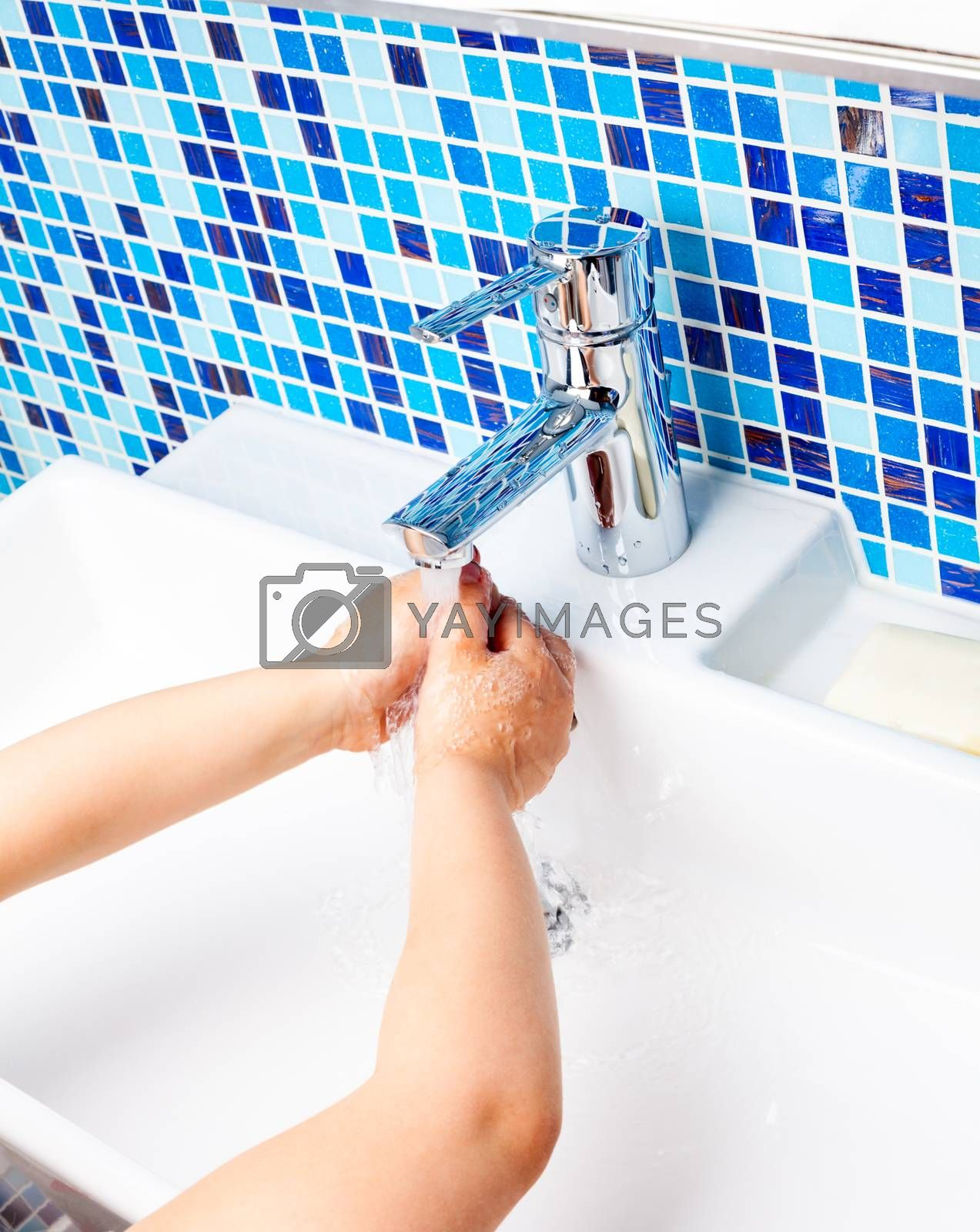 Girl washing her hands in a bathroom sink