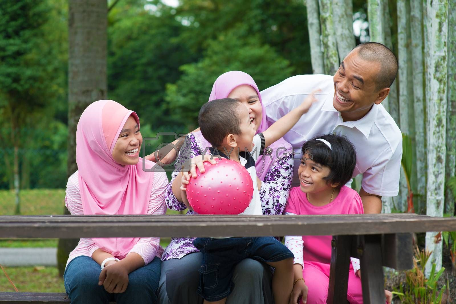Happy Southeast Asian family sitting at garden bench having fun, outdoor lifestyle at nature green park.