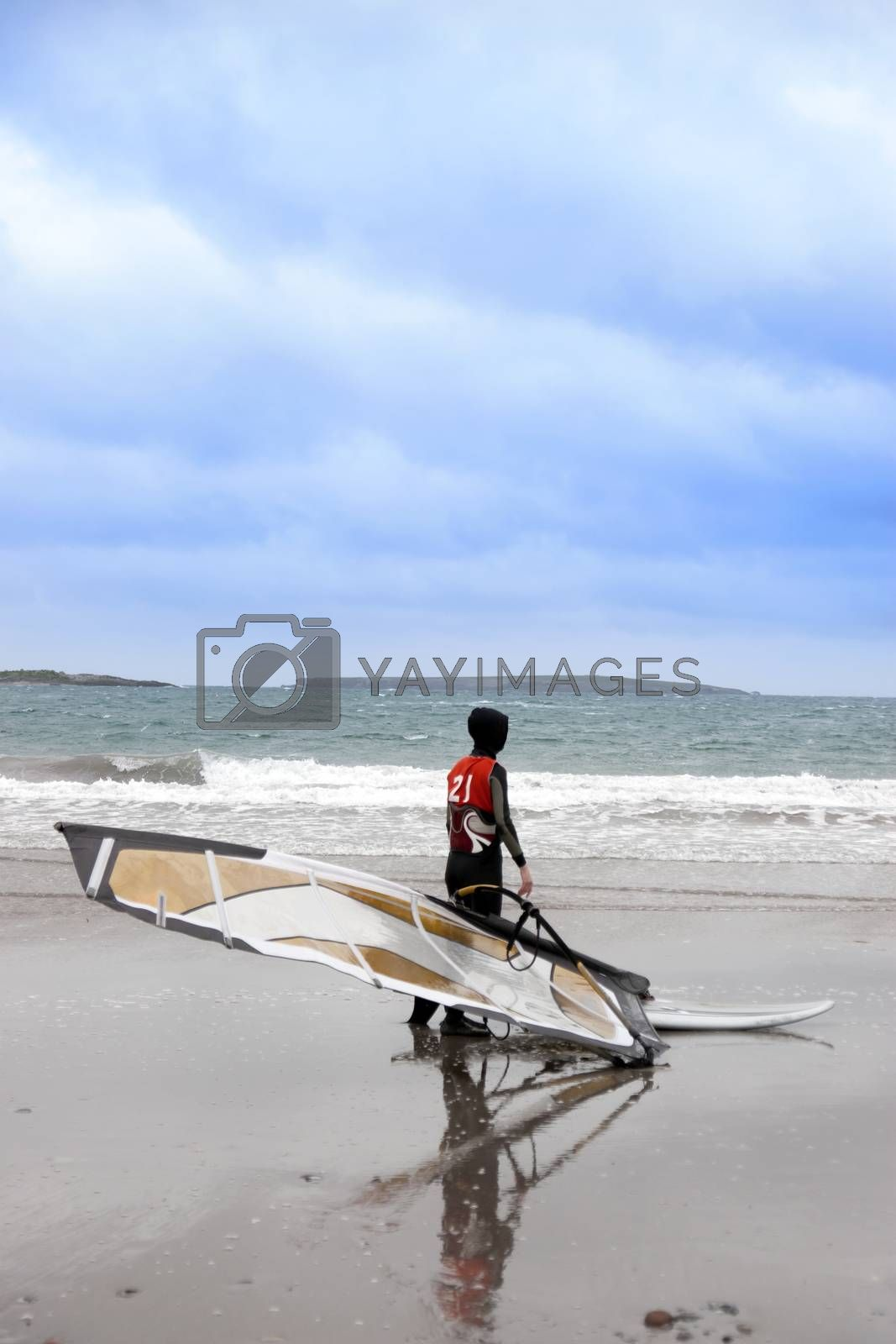 lone windsurfer getting ready to surf on the beach in the maharees county kerry ireland