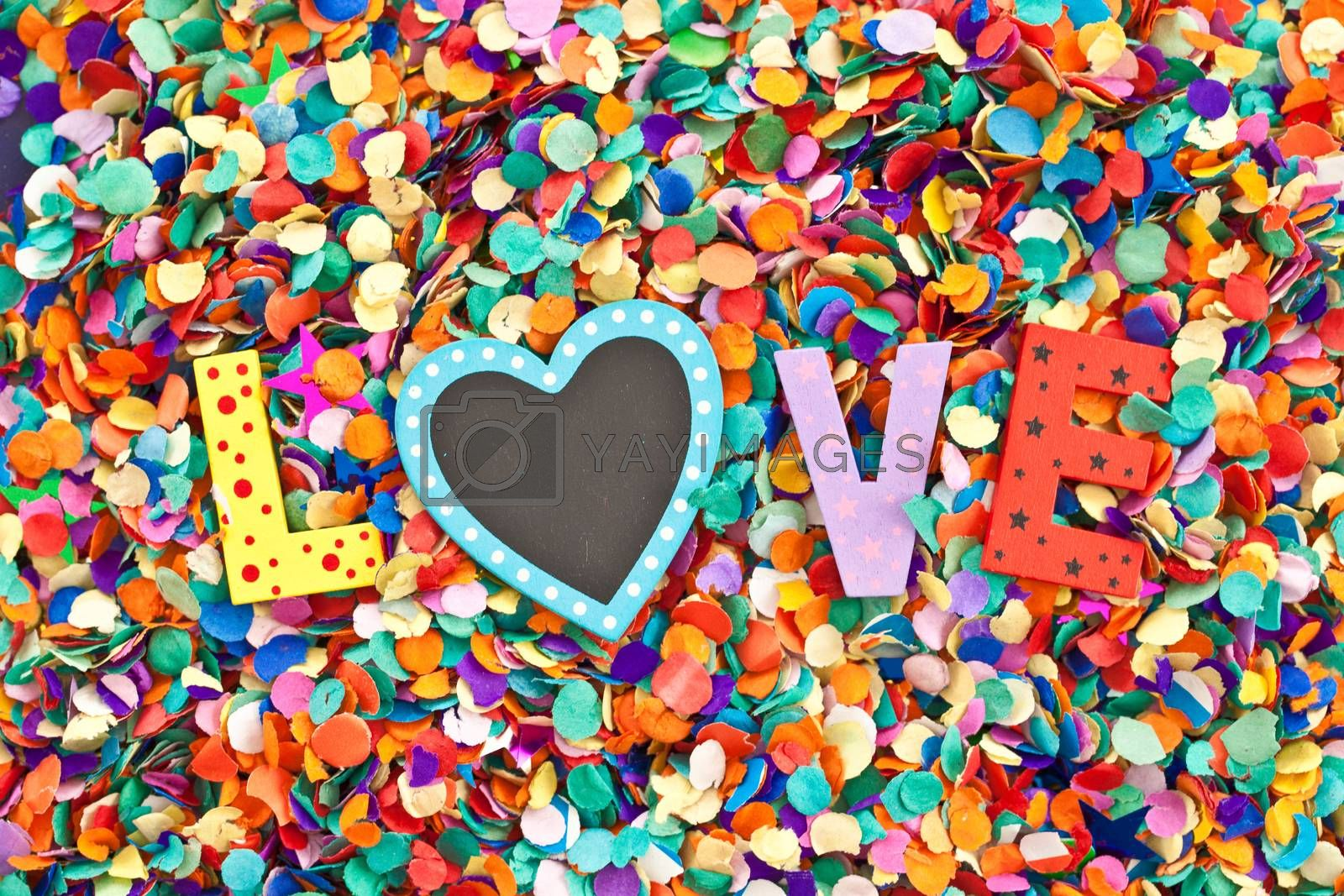 Love in colorful wooden characters on background of confetti