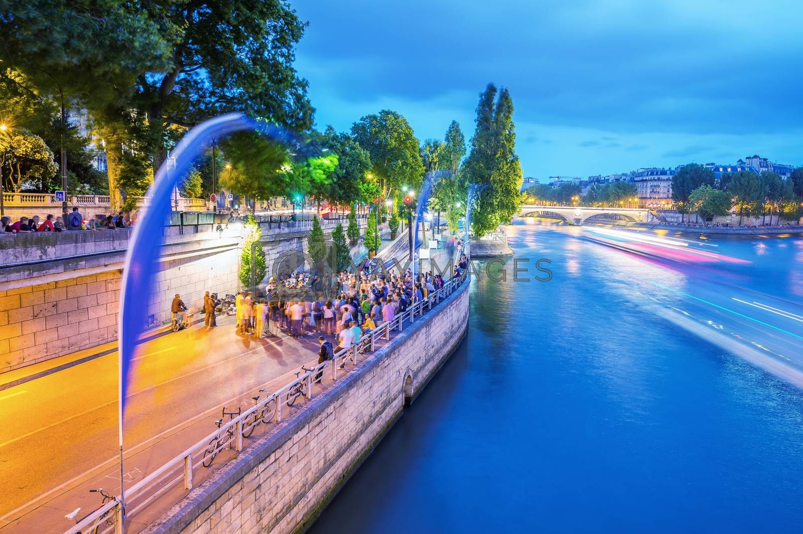 PARIS - JUNE 13, 2014: Tourists along Seine river at dusk. More than 30 million people visit the city every year.