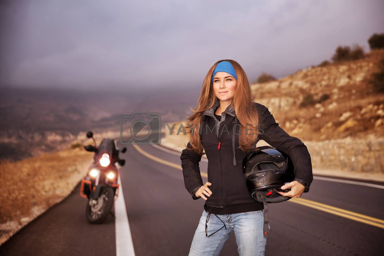 Fashion biker girl standing on the road with helmet in hands, traveling in overcast weather, active lifestyle concept