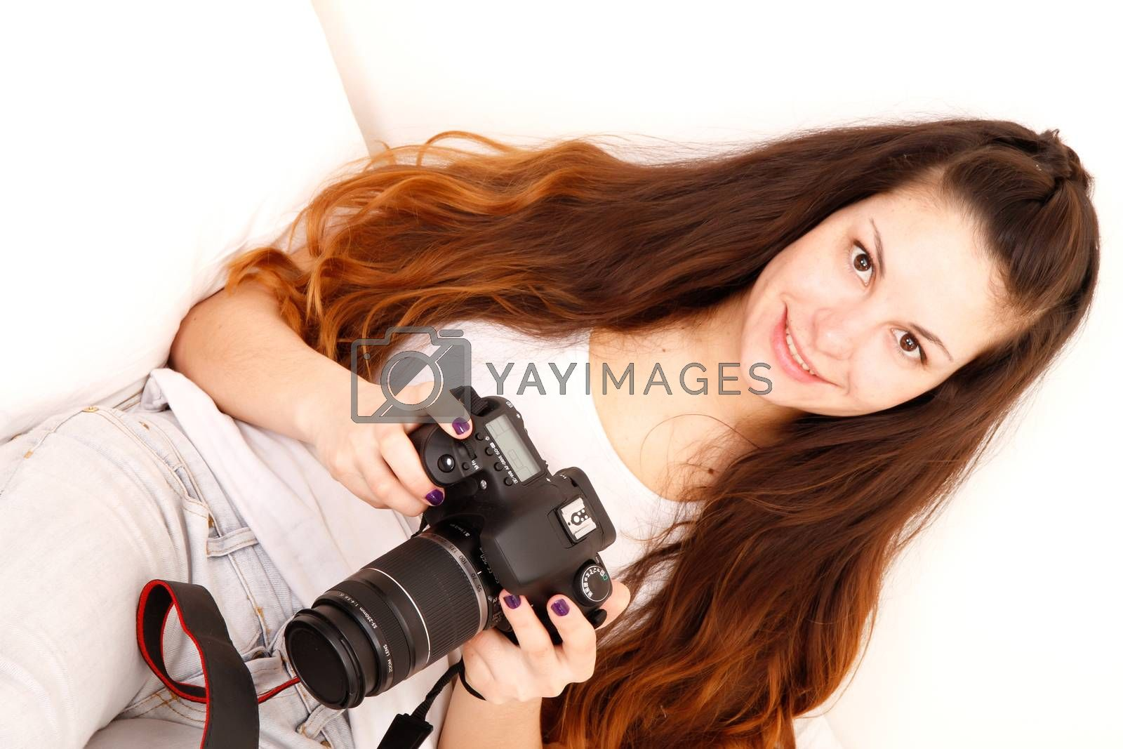A young hispanic girl with DSLR camera in the bed.