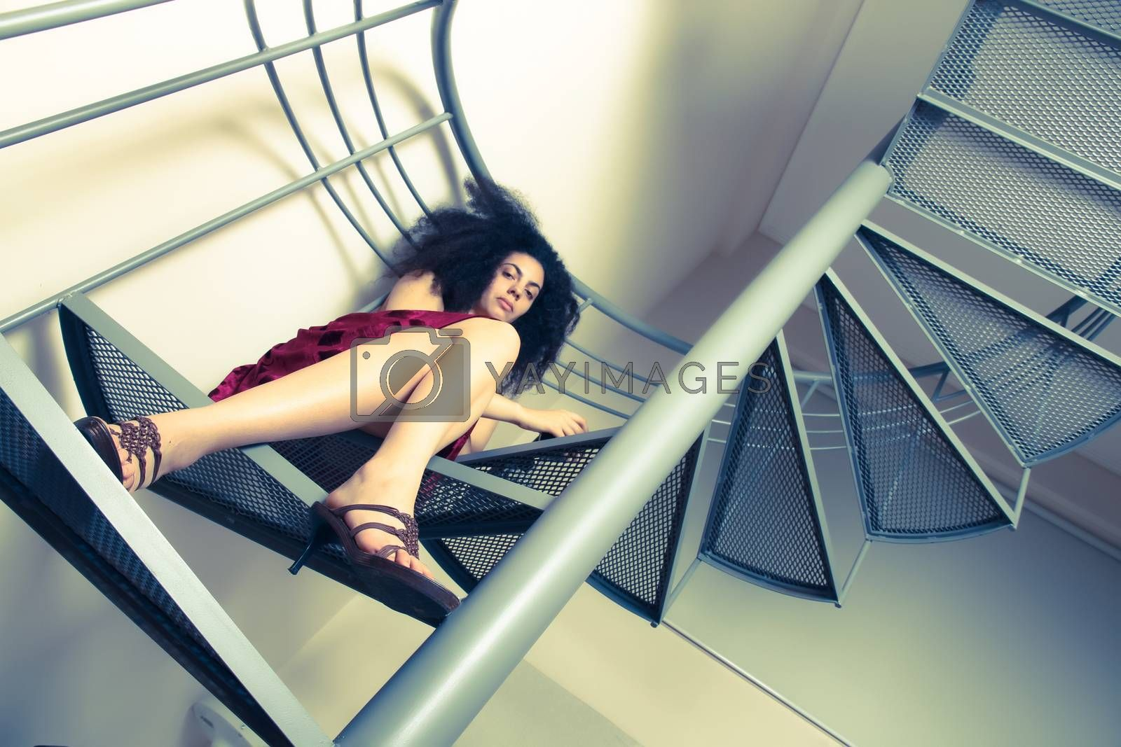 A young brazilian woman sitting on the stairs with a glass of red wine.
