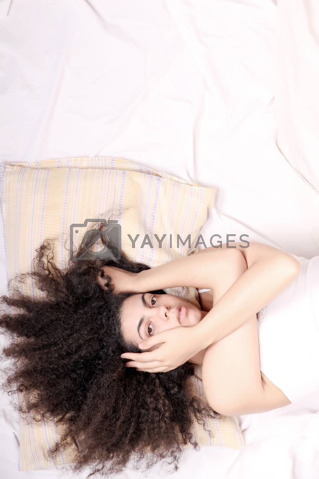 A young latin woman lying down in bed.