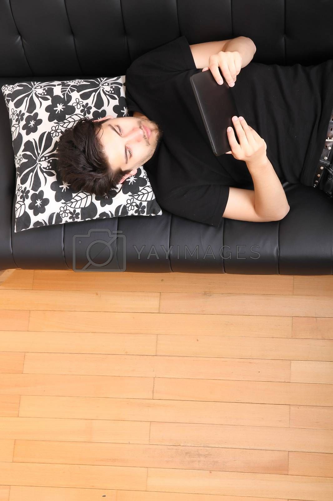 A young hispanic man lying on the sofa holding a Tablet PC.
