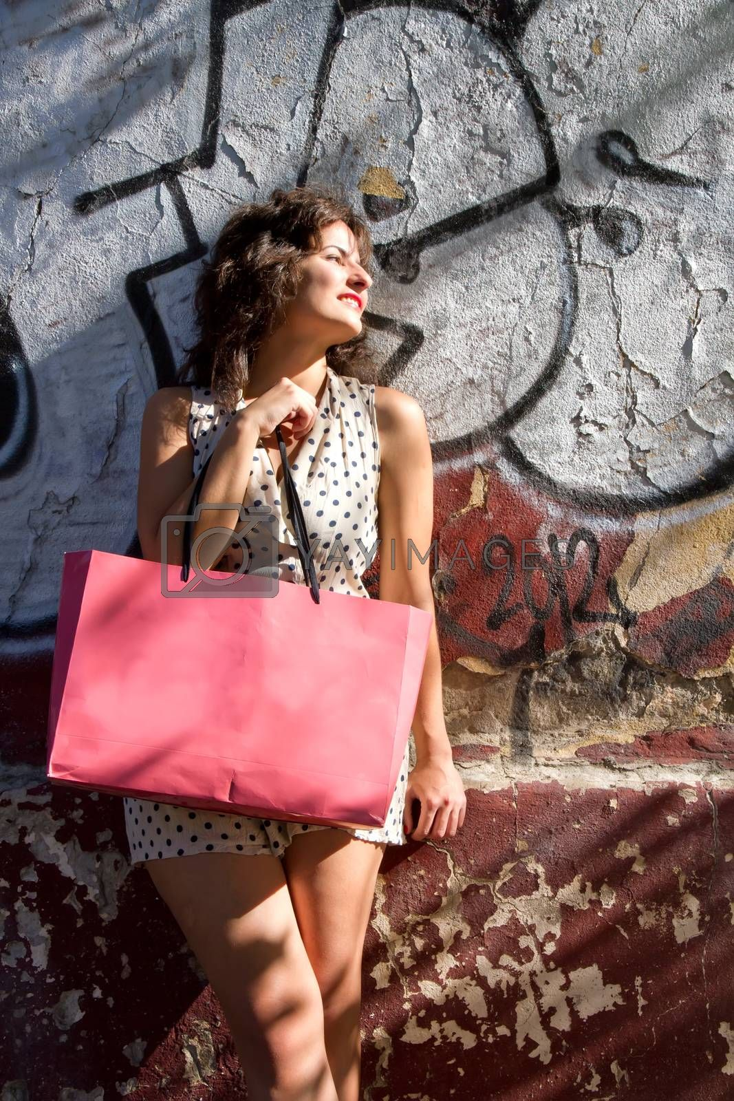 A young adult woman with a shopping bag in an urban environment.