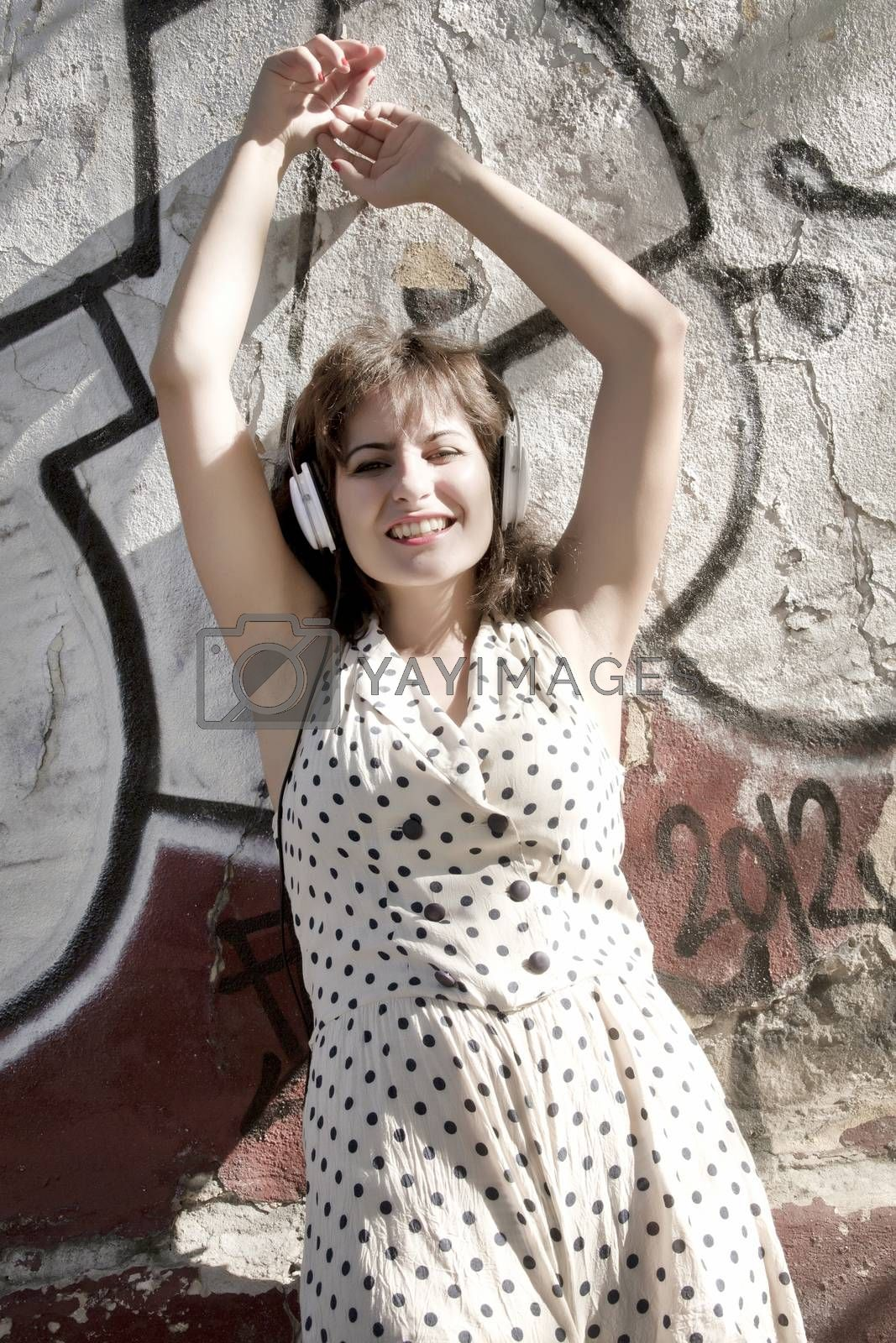 A vintage dressed girl listing to music in a urban environment.