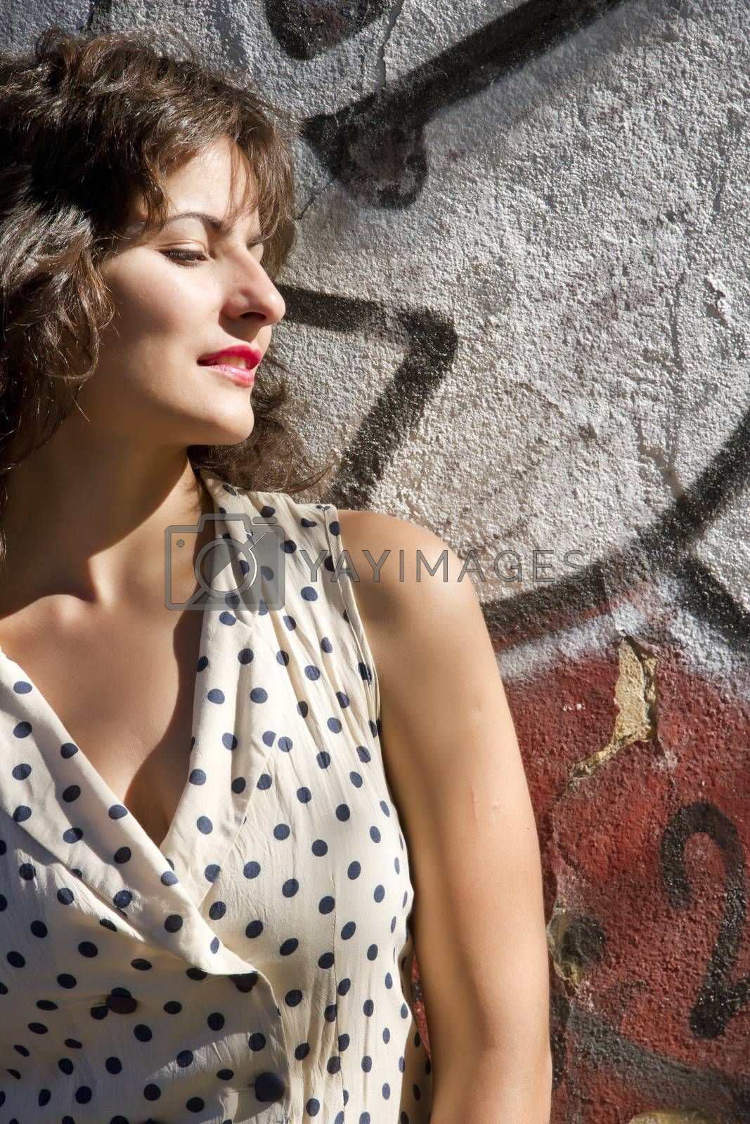 A vintage style dressed girl leaning at a graffiti wall and enjoying the sunlight.
