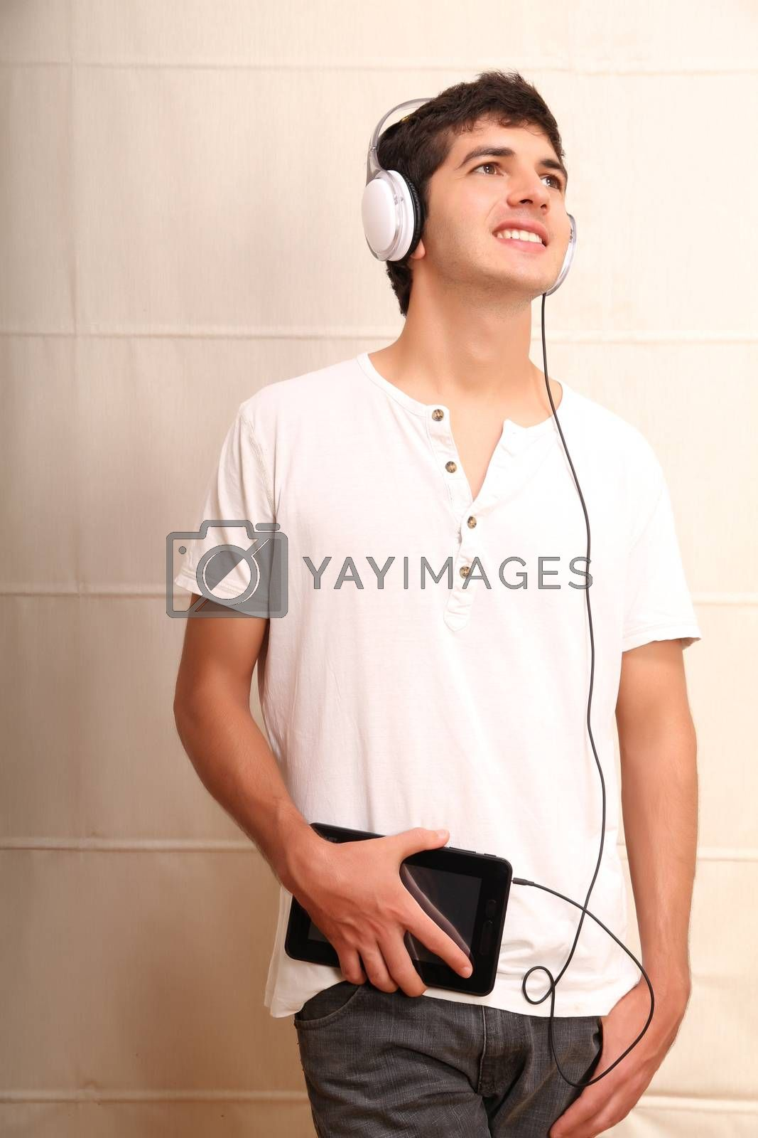 A young, latin man with a Tablet PC and headphones