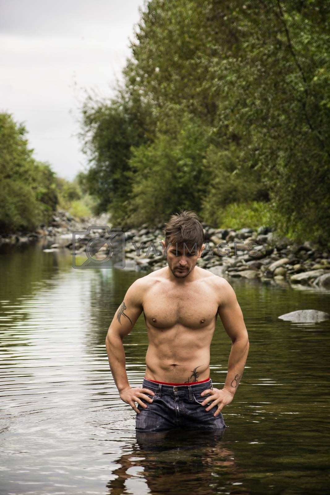 Handsome young muscle man standing in water pond, naked by artofphoto