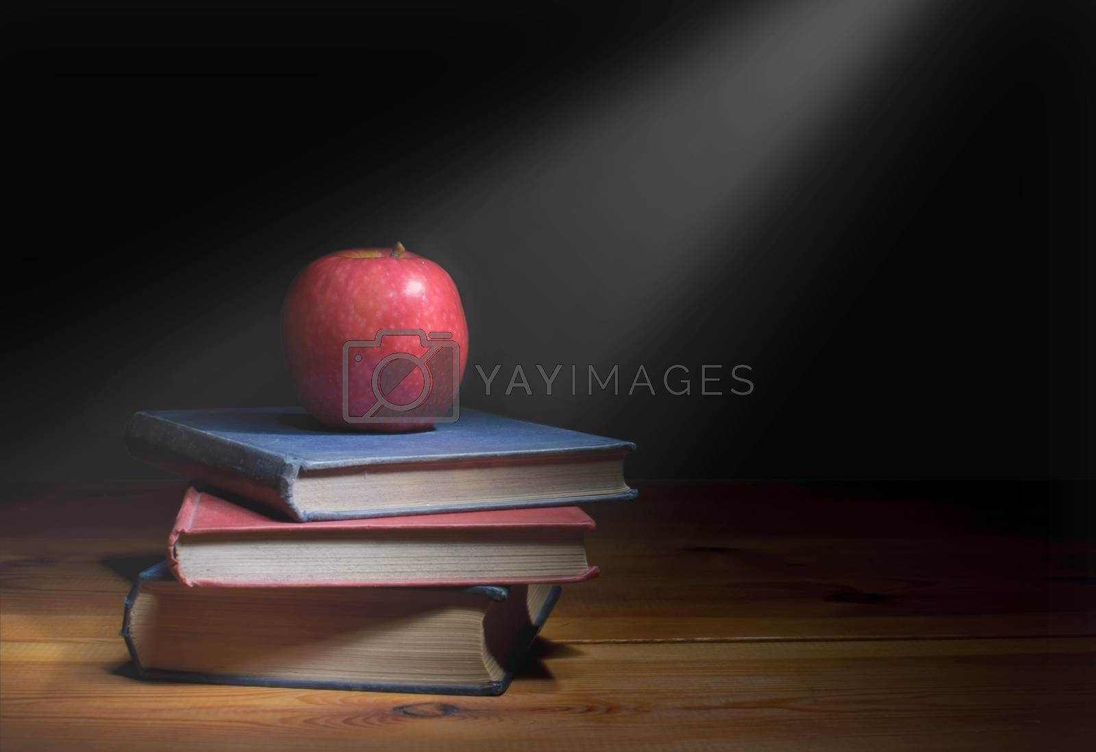 Ray of light shining down on a stack of books with a red apple