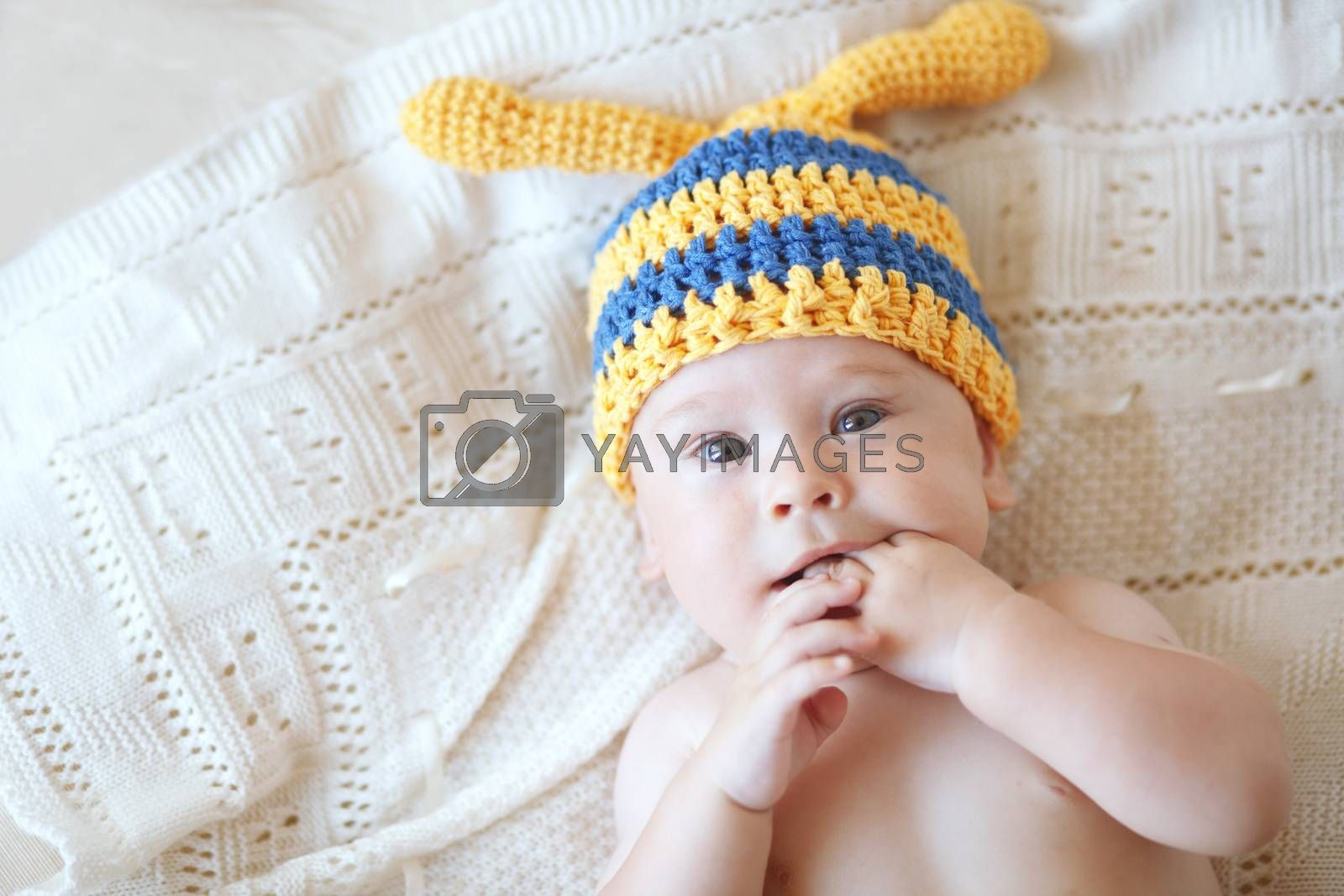Portrait of a cute 4 months baby wearing crochet knit hat, top view point