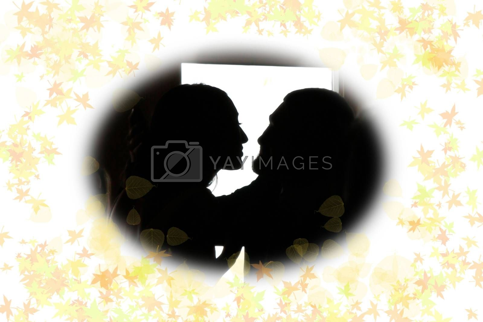 young loving couple holding each other in silhouette with leafy frame gazing into each others eyes