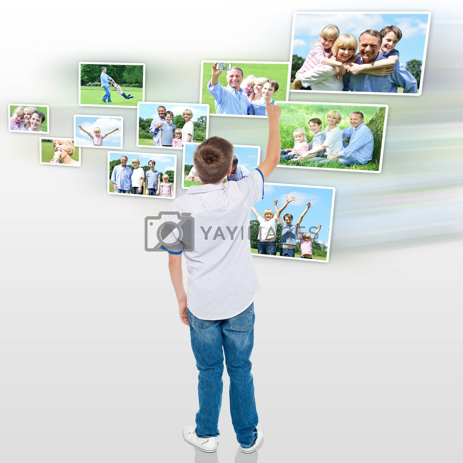Rear view of boy looking his pictures in virtual screen