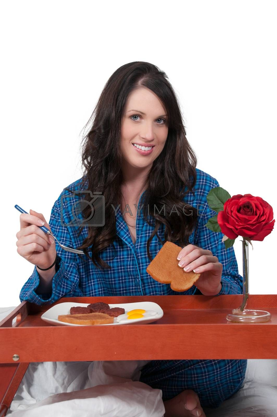 Beautiful woman eating a big breakfast in bed