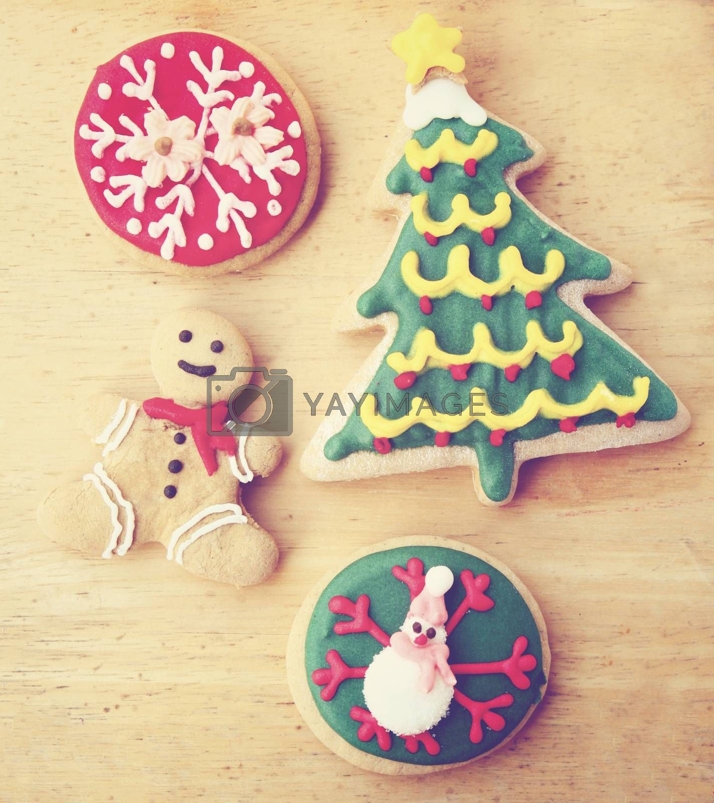 Decorated christmas gingerbreads on wooden background with retro filter effect