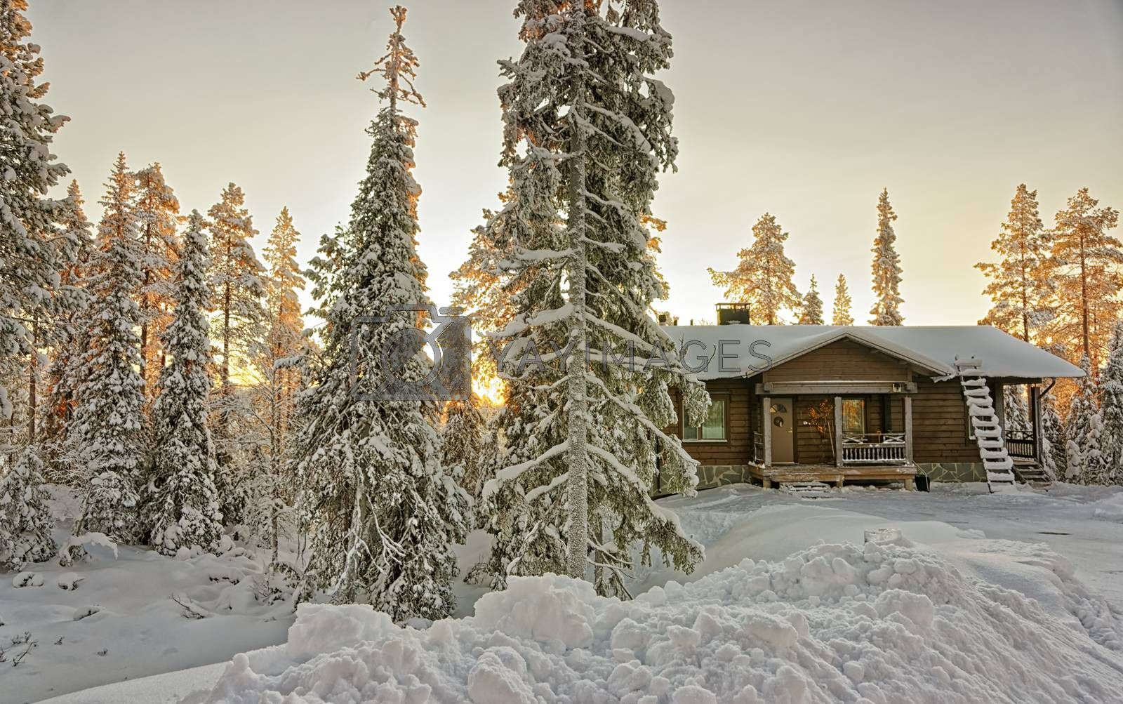 Cottage in snowy winter forest at sunset