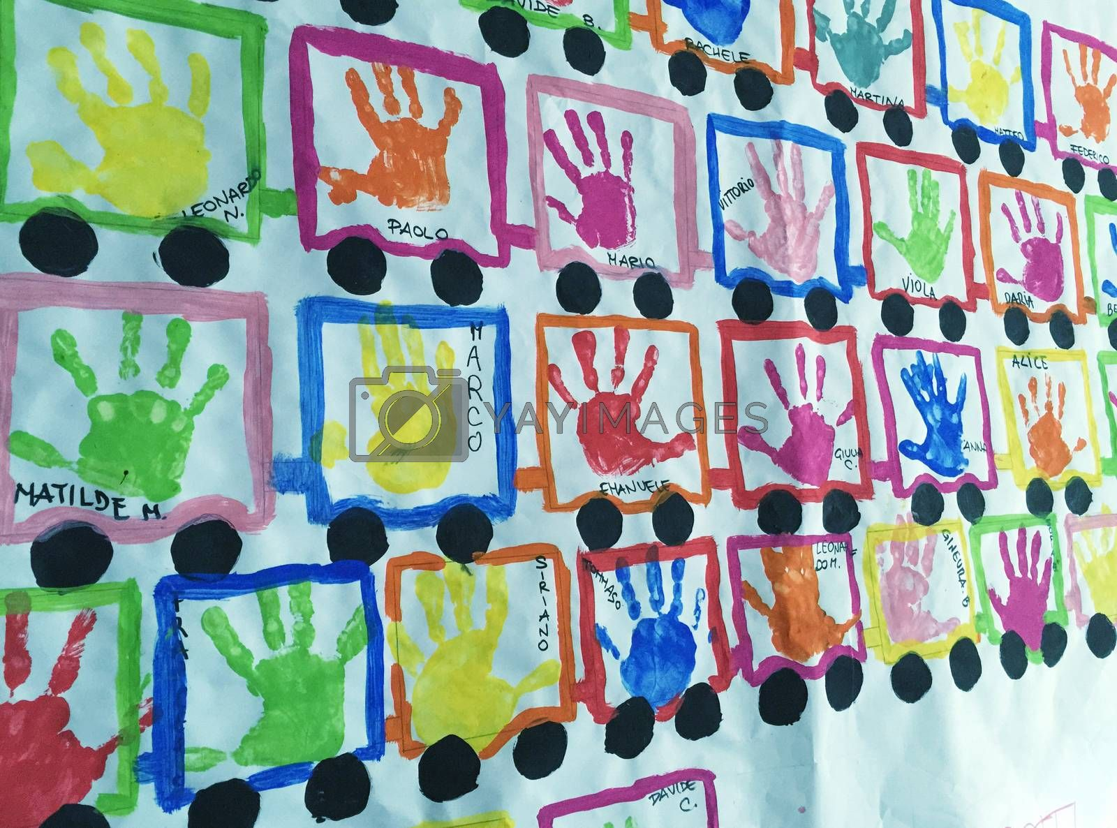 Baby names and handprints on a school wall.
