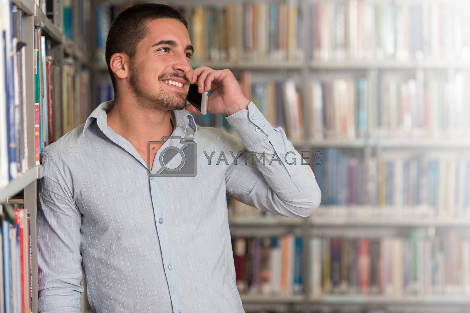 Male Student Talking On The Phone In Library - Shallow Depth Of Field
