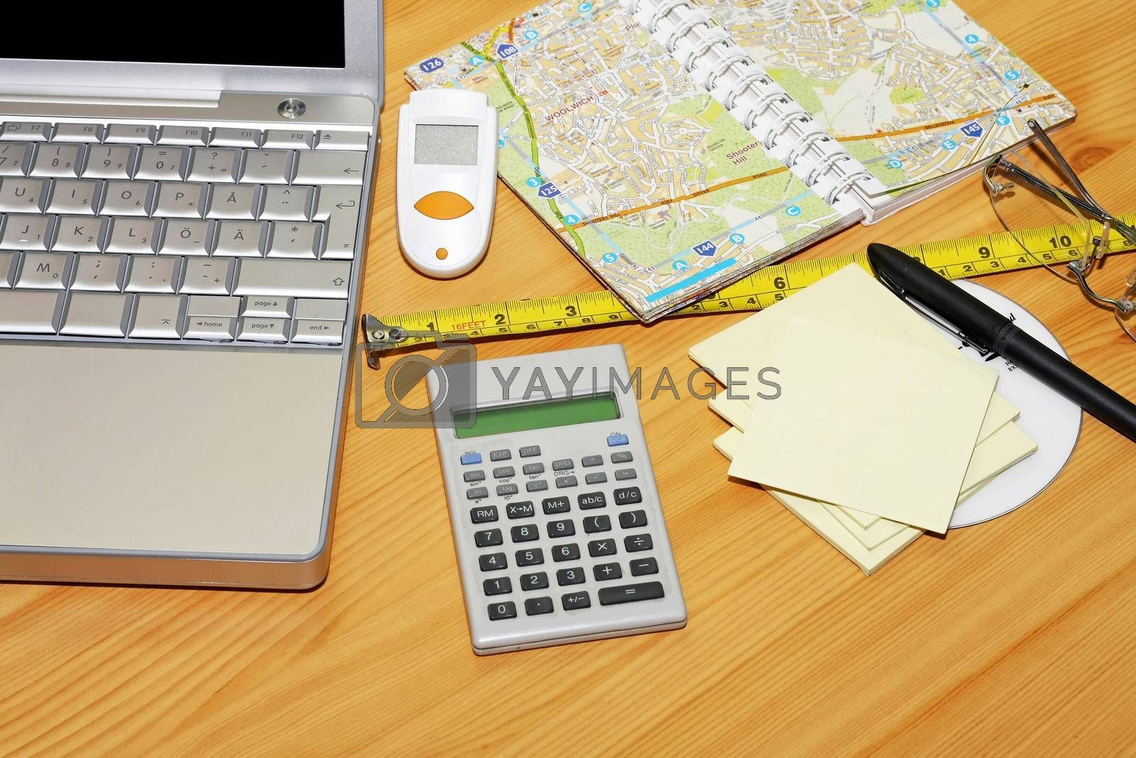 Notebook map and calculator at wooden desk