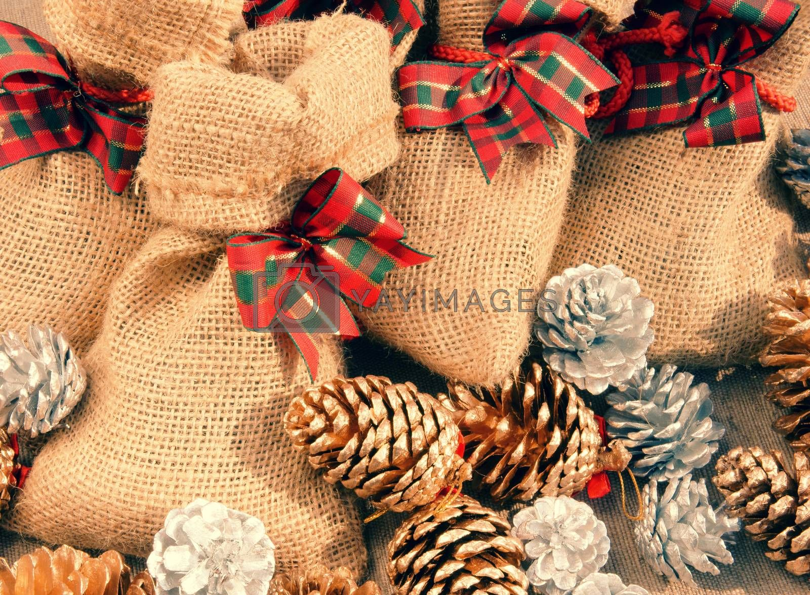 Xmas gift and pine cone in basket, decoration for christmas season, present bag from burlap, with amazing knot