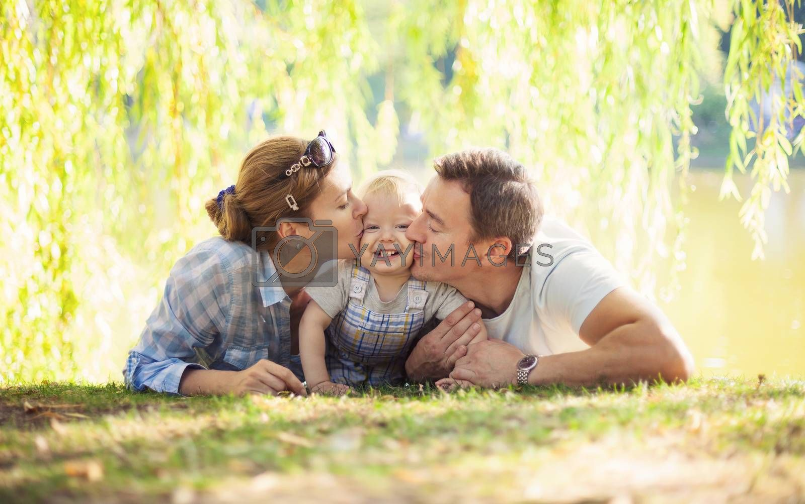 Happy parents kissing toddler boy. Father, mother and son relaxing on the lawn.