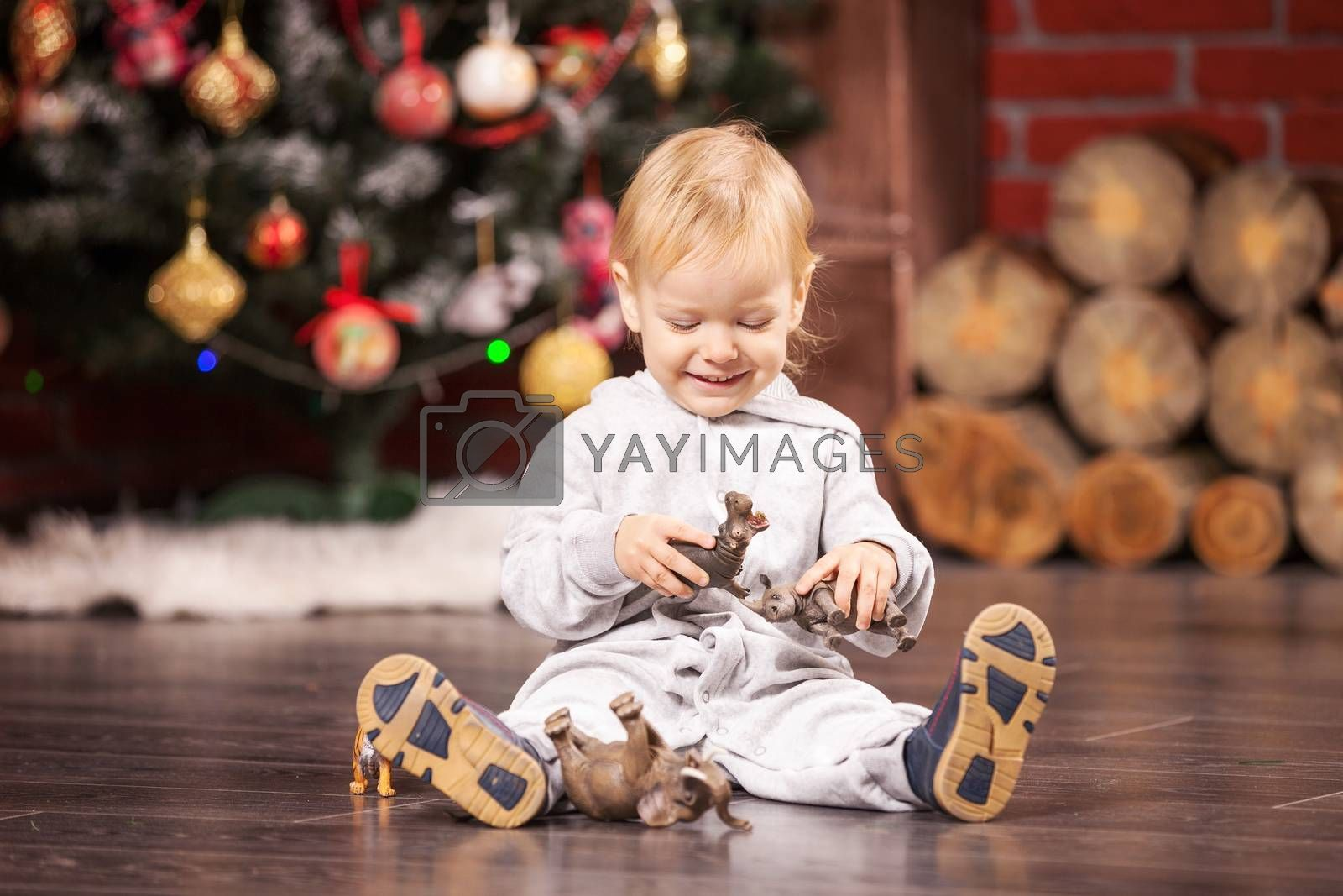 Cheerful little boy playing with his toy animals by Christmas tree