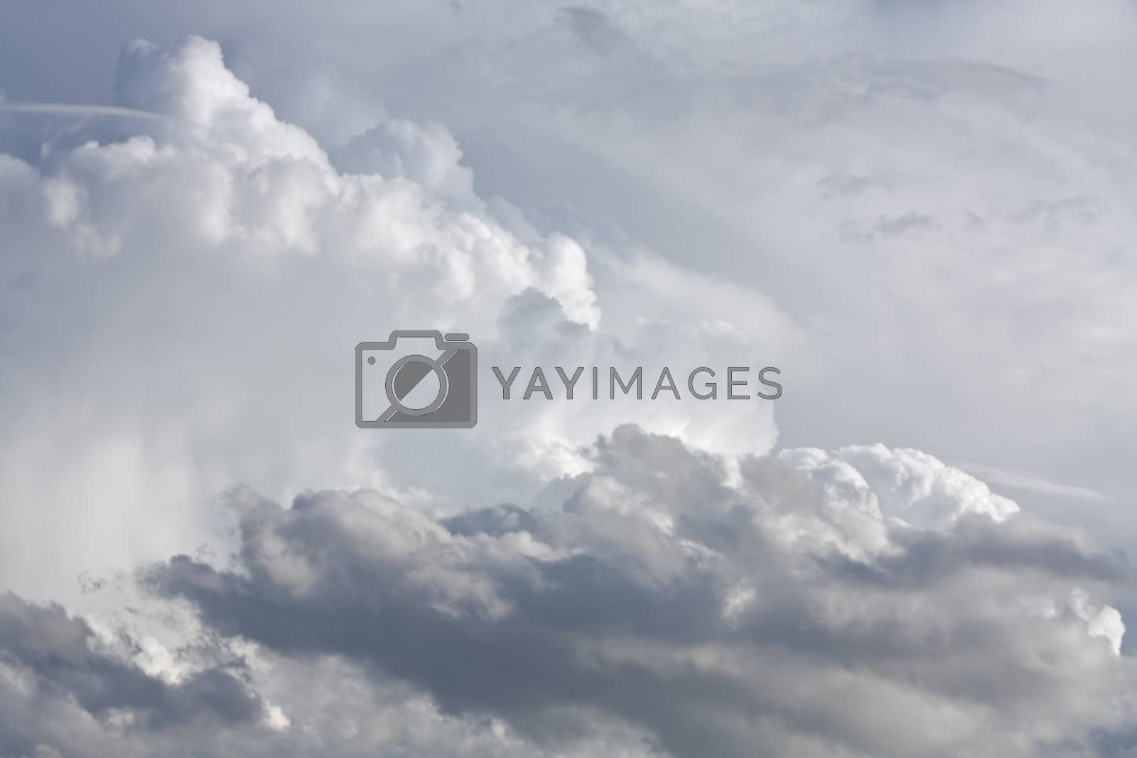 white and dark cumulus clouds against a bright blue sky without the sun