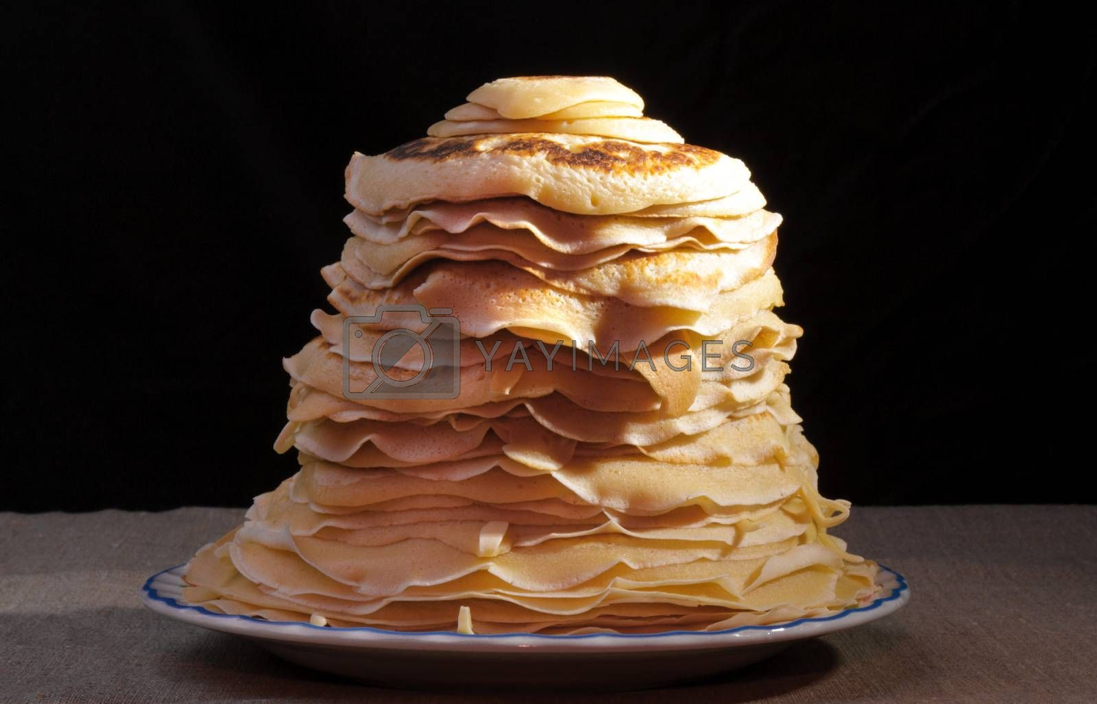 Pile of pancakes with an oil slice on a plate on black