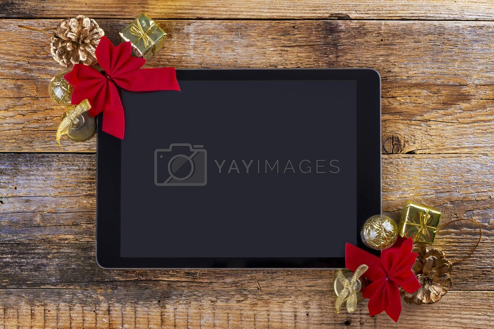 Royalty free image of tablet pc with  christmas decorations on wooden background by manaemedia