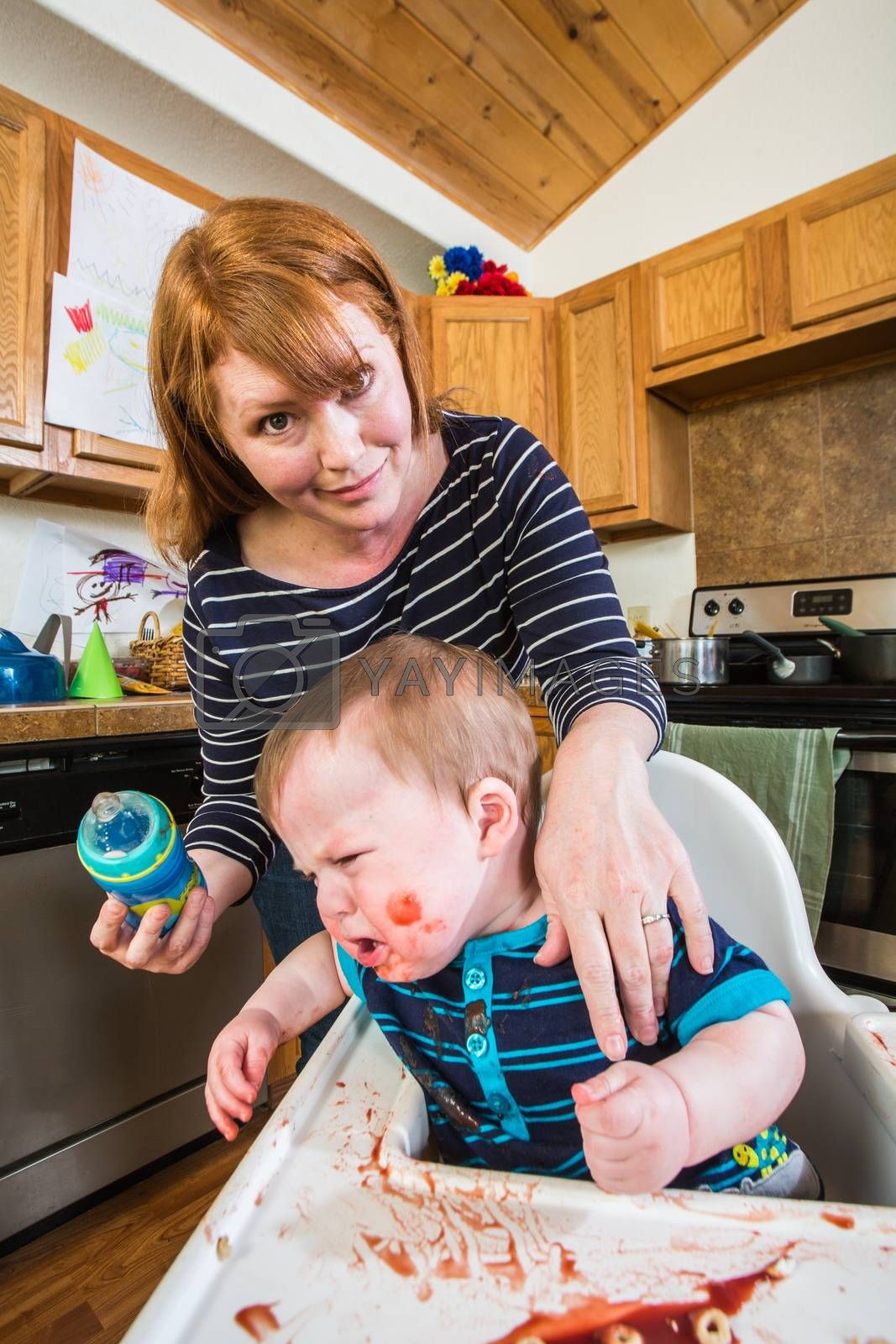 Royalty free image of Woman Feeds Her Gumpy Baby by Creatista