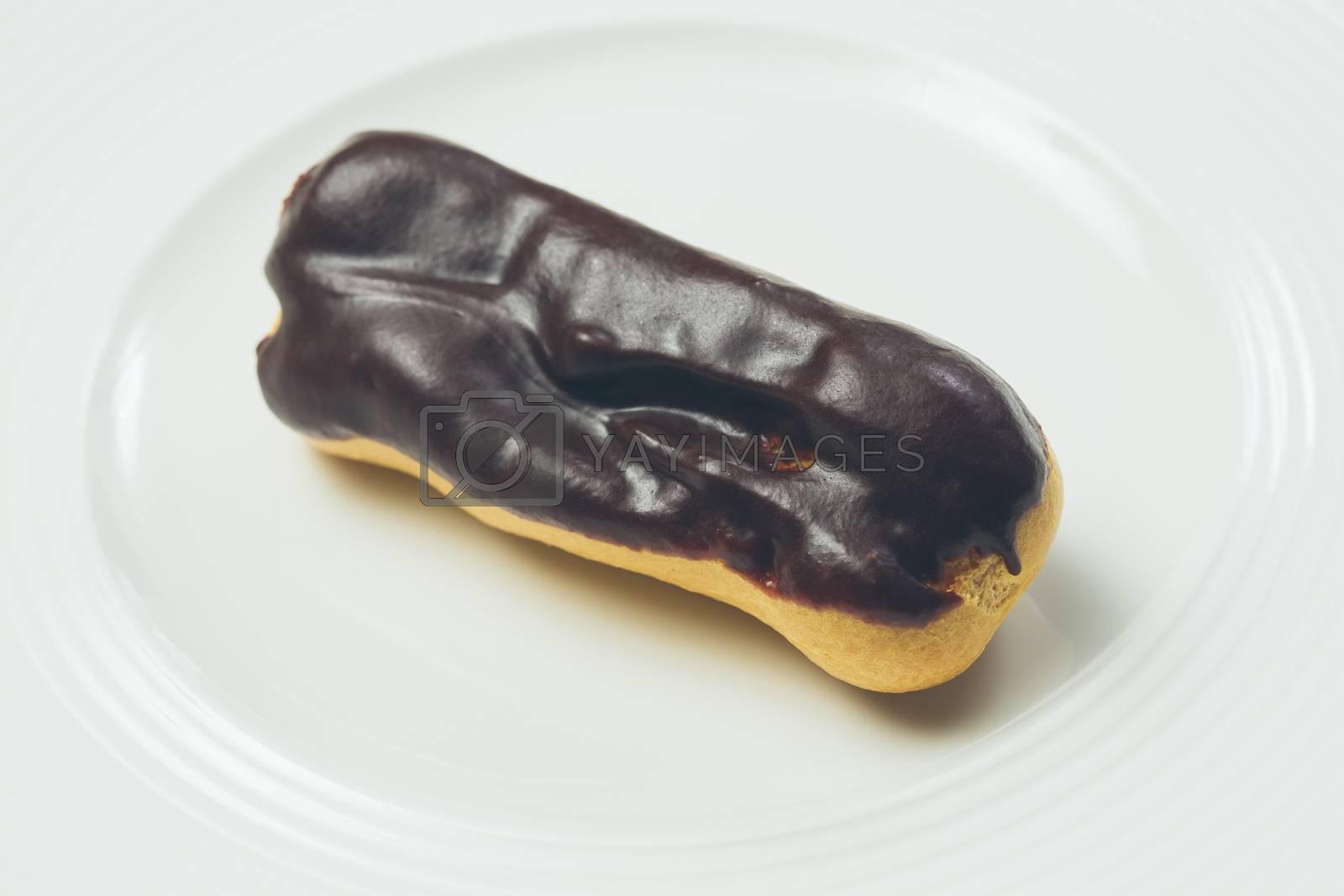 Royalty free image of Single chocolate eclair on white  plate by sarymsakov