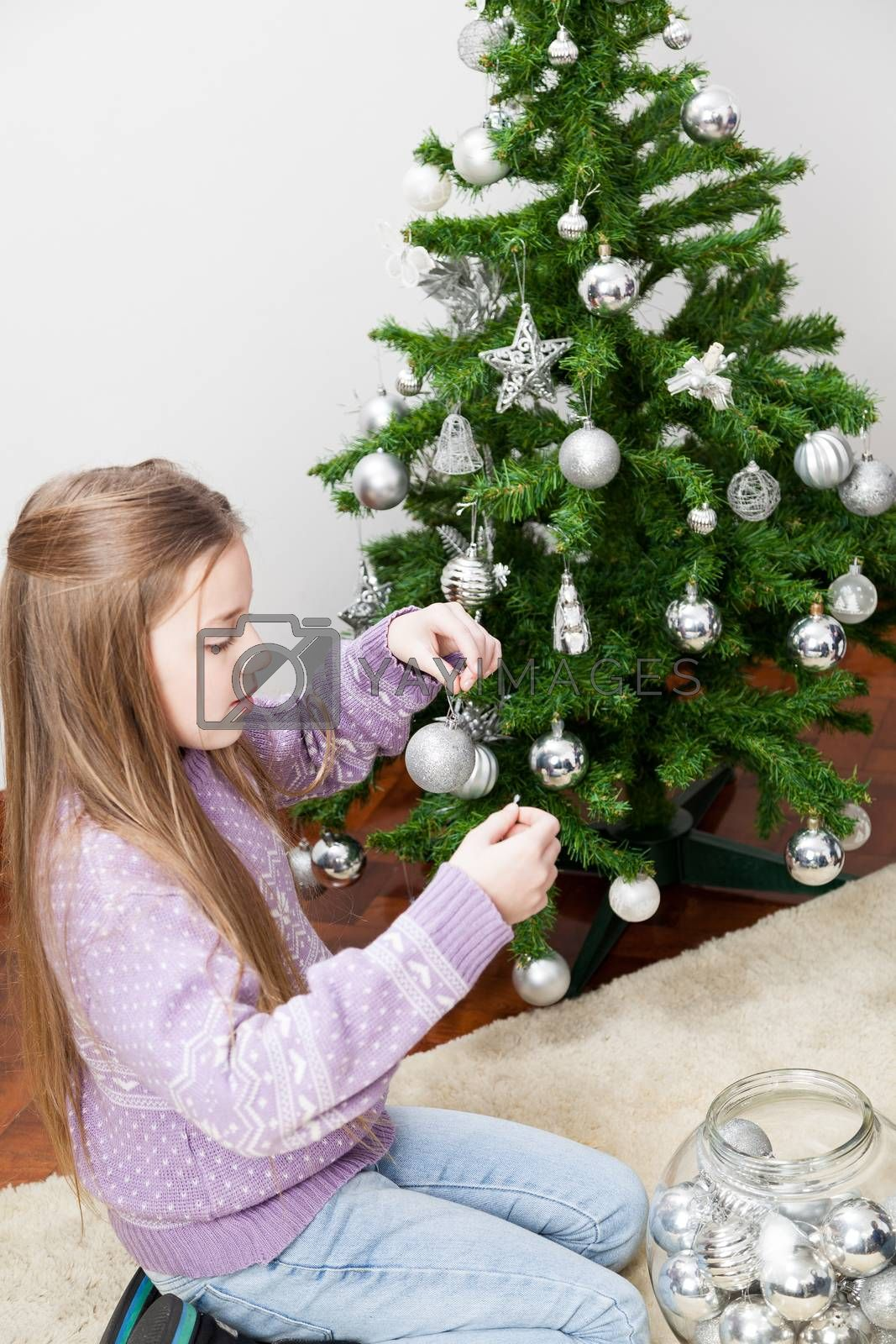 Girl putting balls on the christmas tree by ifilms