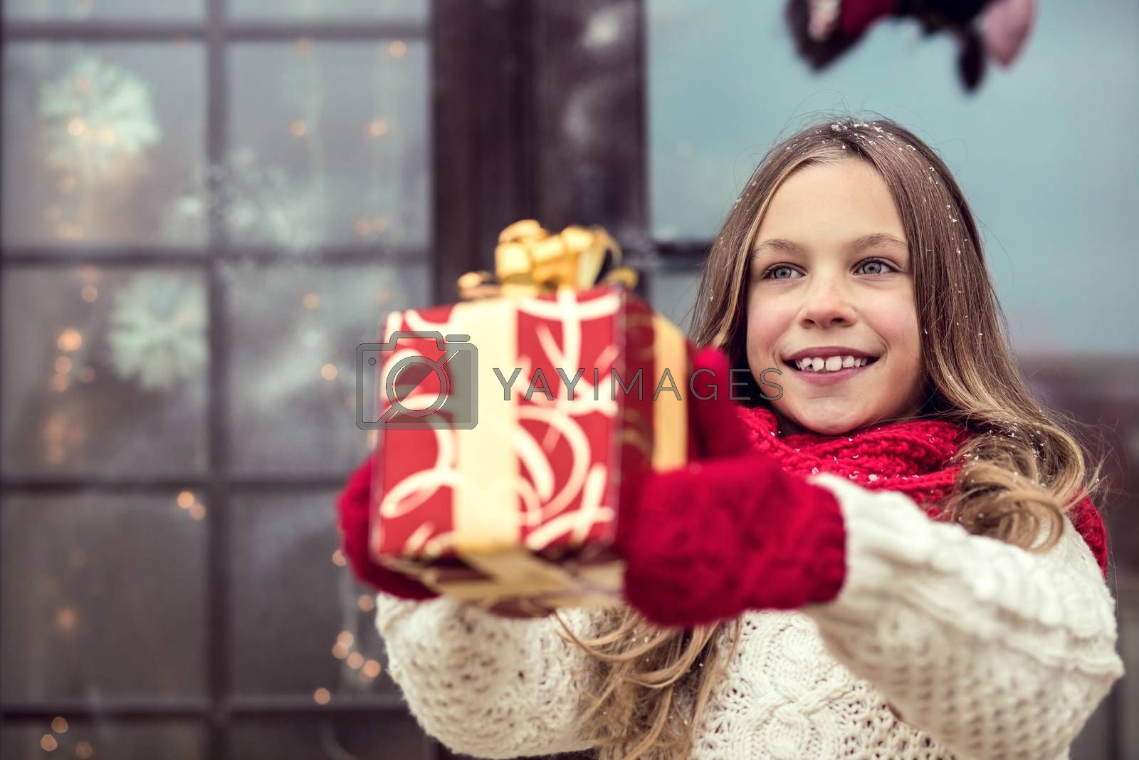 Child giving a Christmas present near her house windows, snowy outside