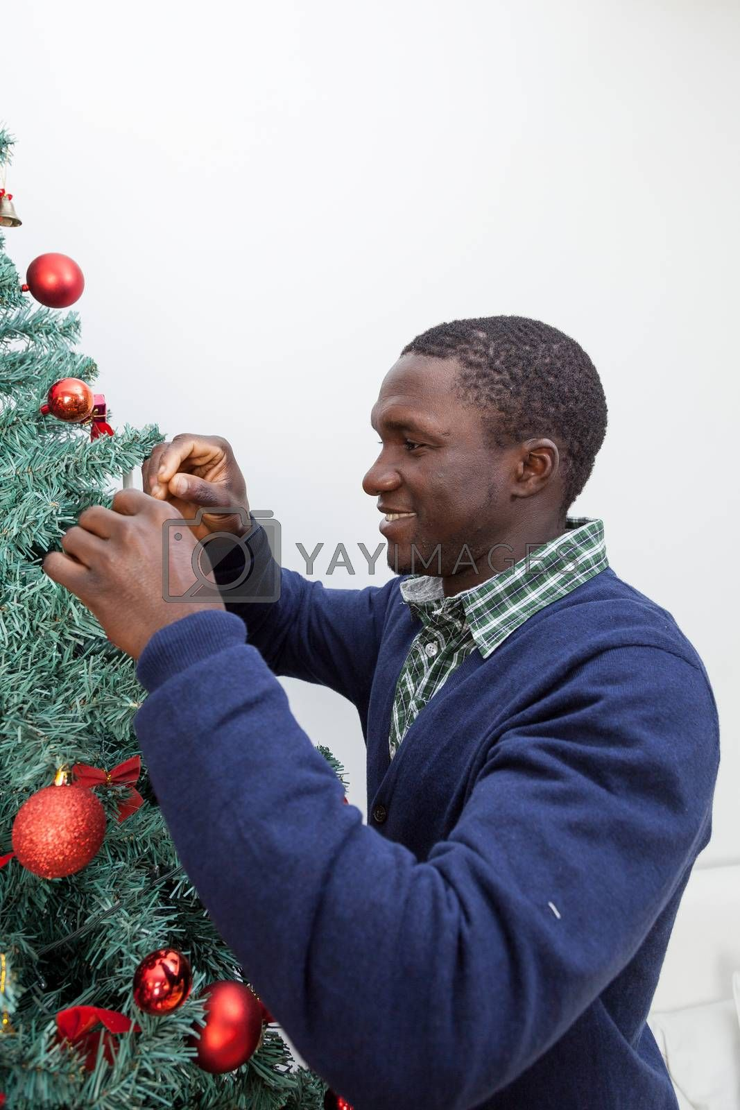 Black man decorating the Christmas tree by ifilms