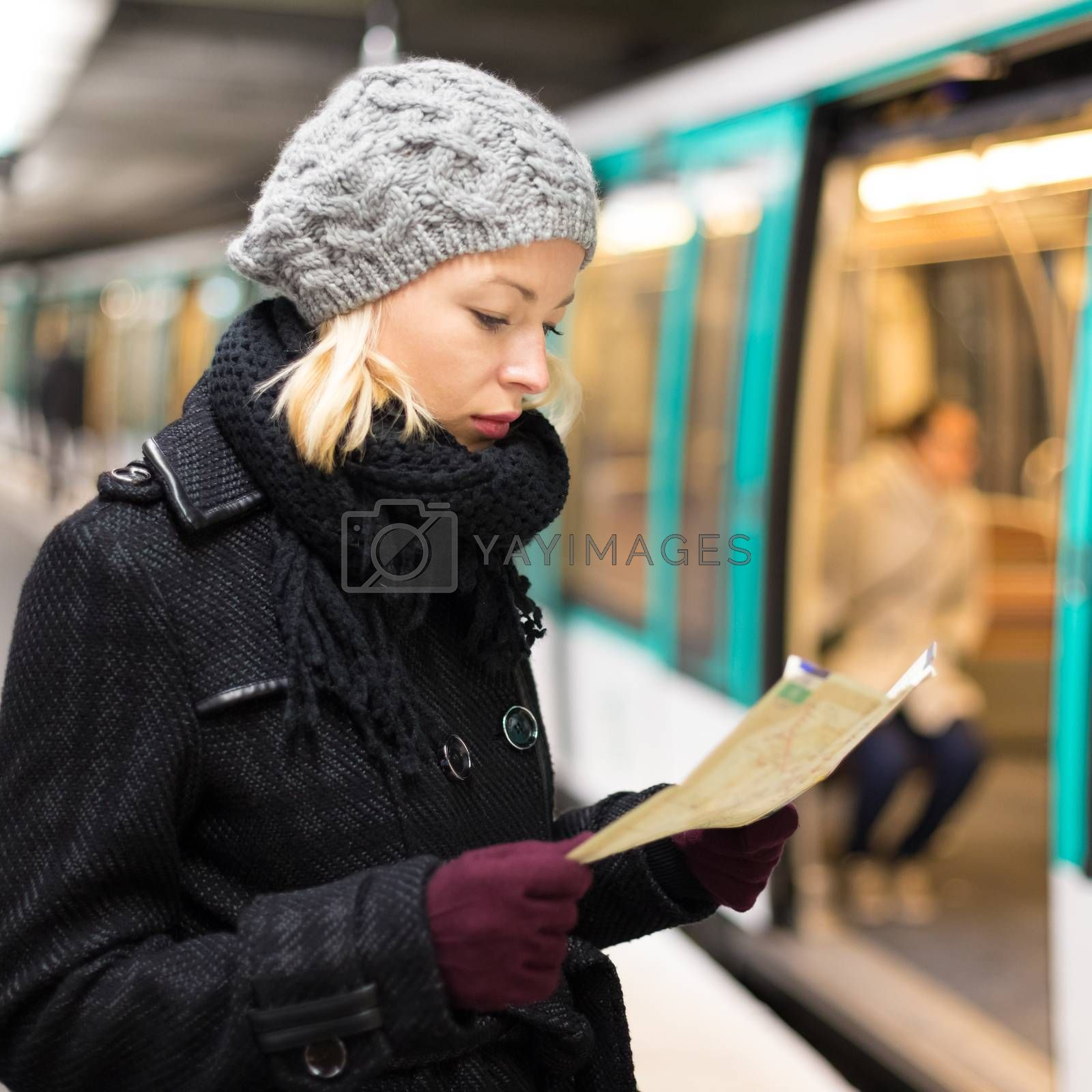 Casually dressed woman wearing winter coat, waiting on a platform for a train to arrive, orientating herself with public transport map. Urban transport.