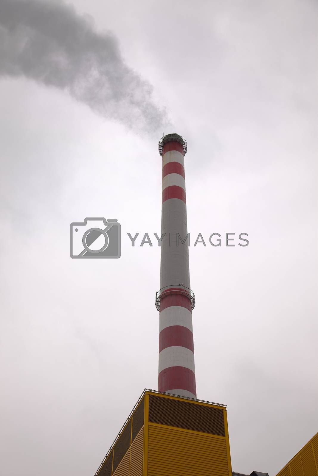 Industrial chimney smoking in the cloudy weather