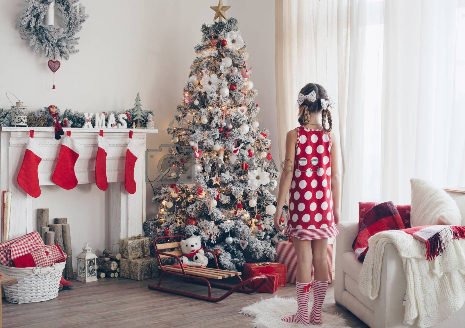 Child girl standing near decorated Christmas tree and fireplace in beautiful hotel room in the holiday morning