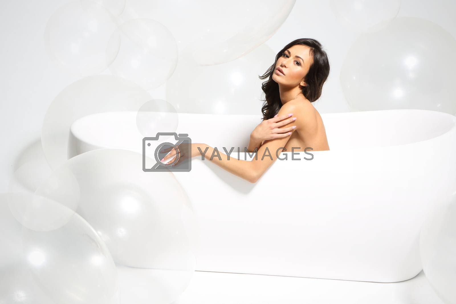 Beautiful hispanic, latino  in a bathtub full of large bubbles