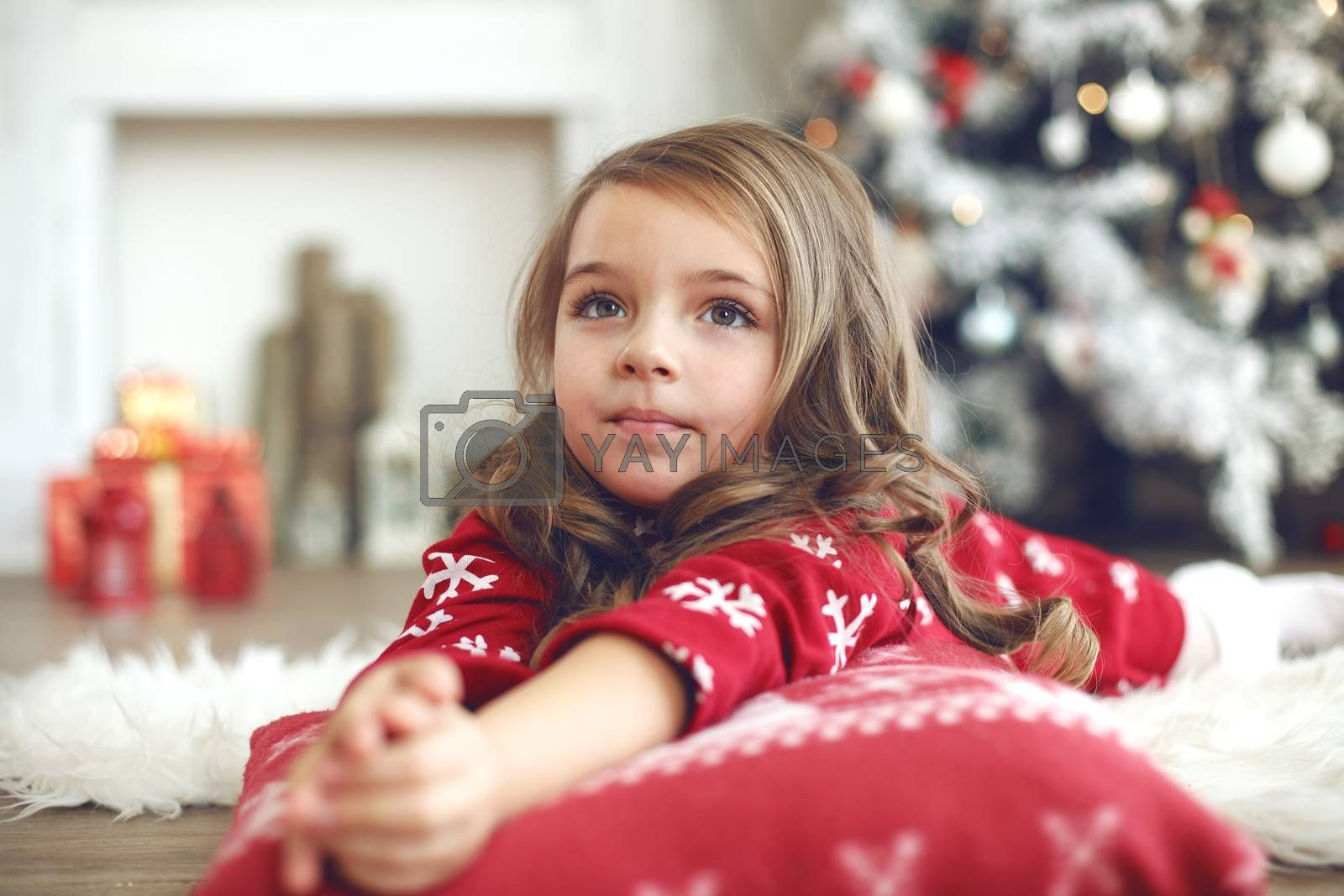 5 years old little girl laying down on soft cushion near Christmas tree at home