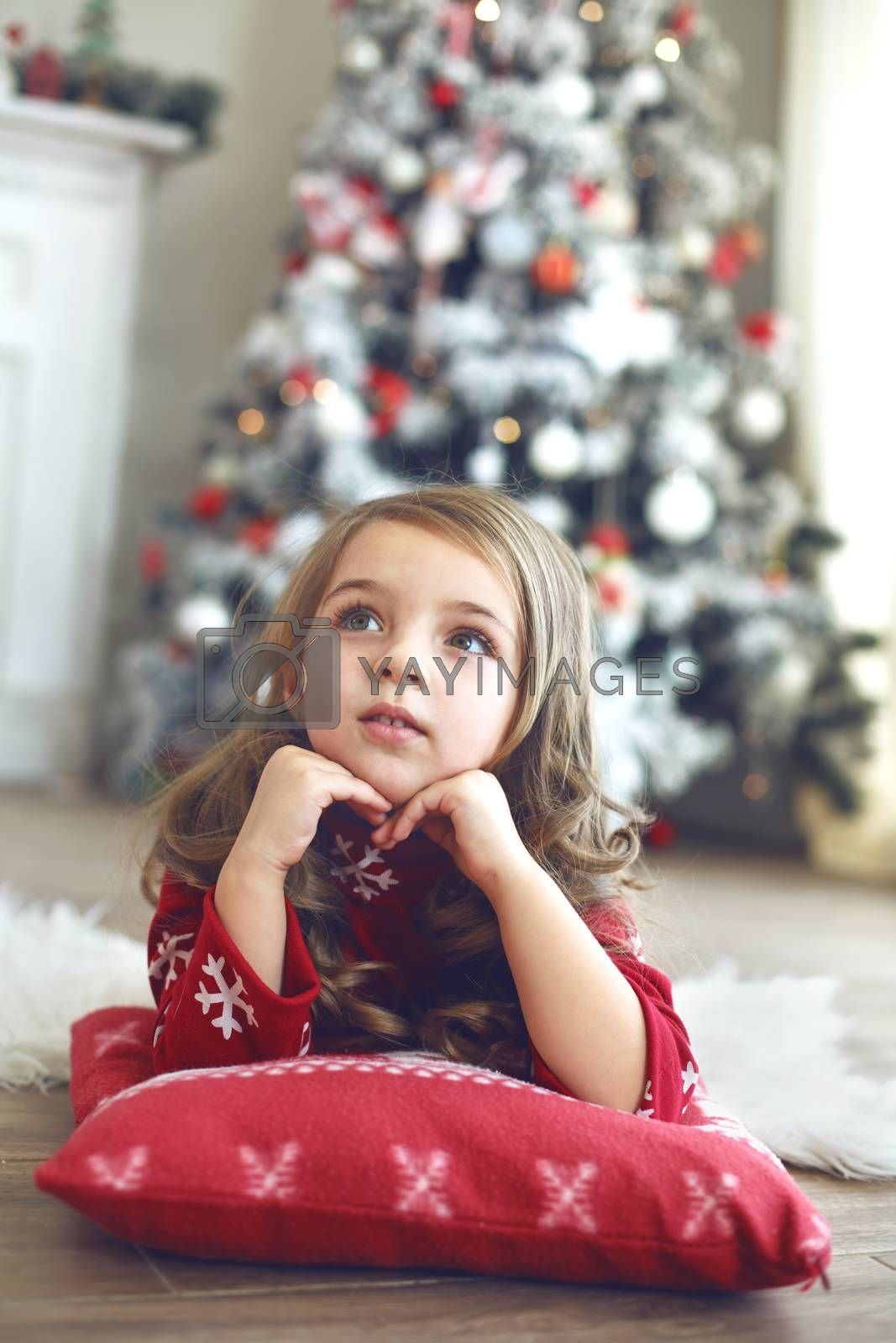 5 years old little girl laying down on soft cushion and looking up near Christmas tree at home