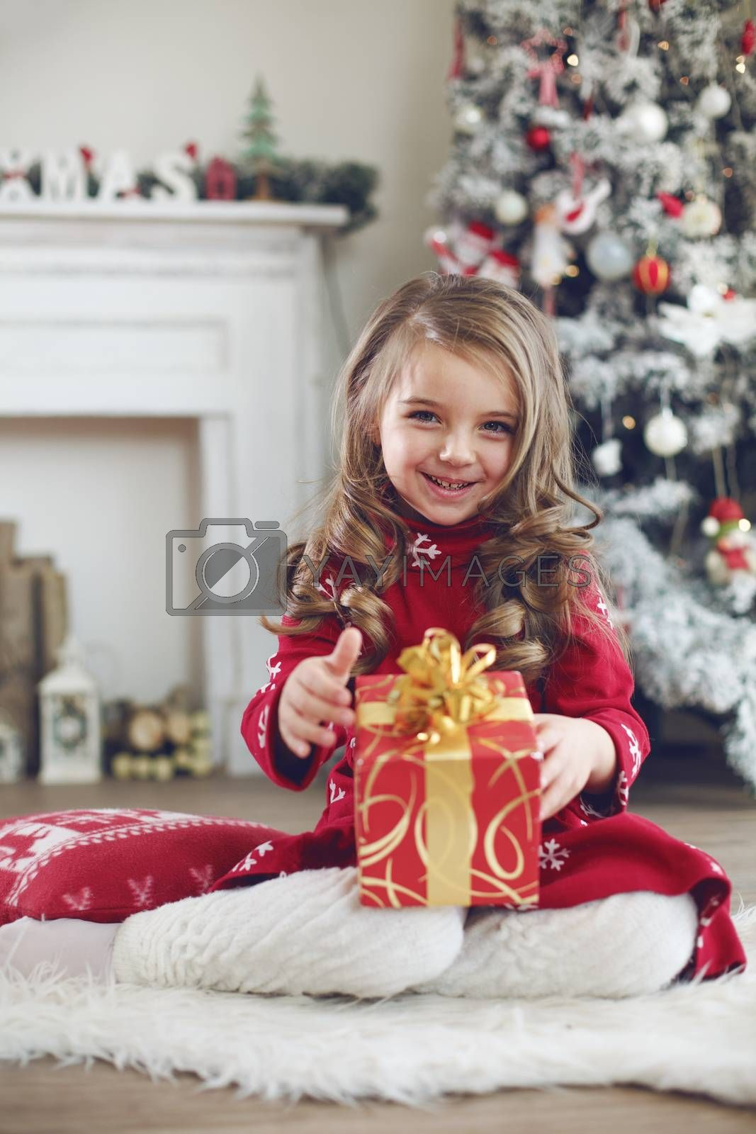 5 years old little girl receives present from Santa Claus near Christmas tree in morning at home