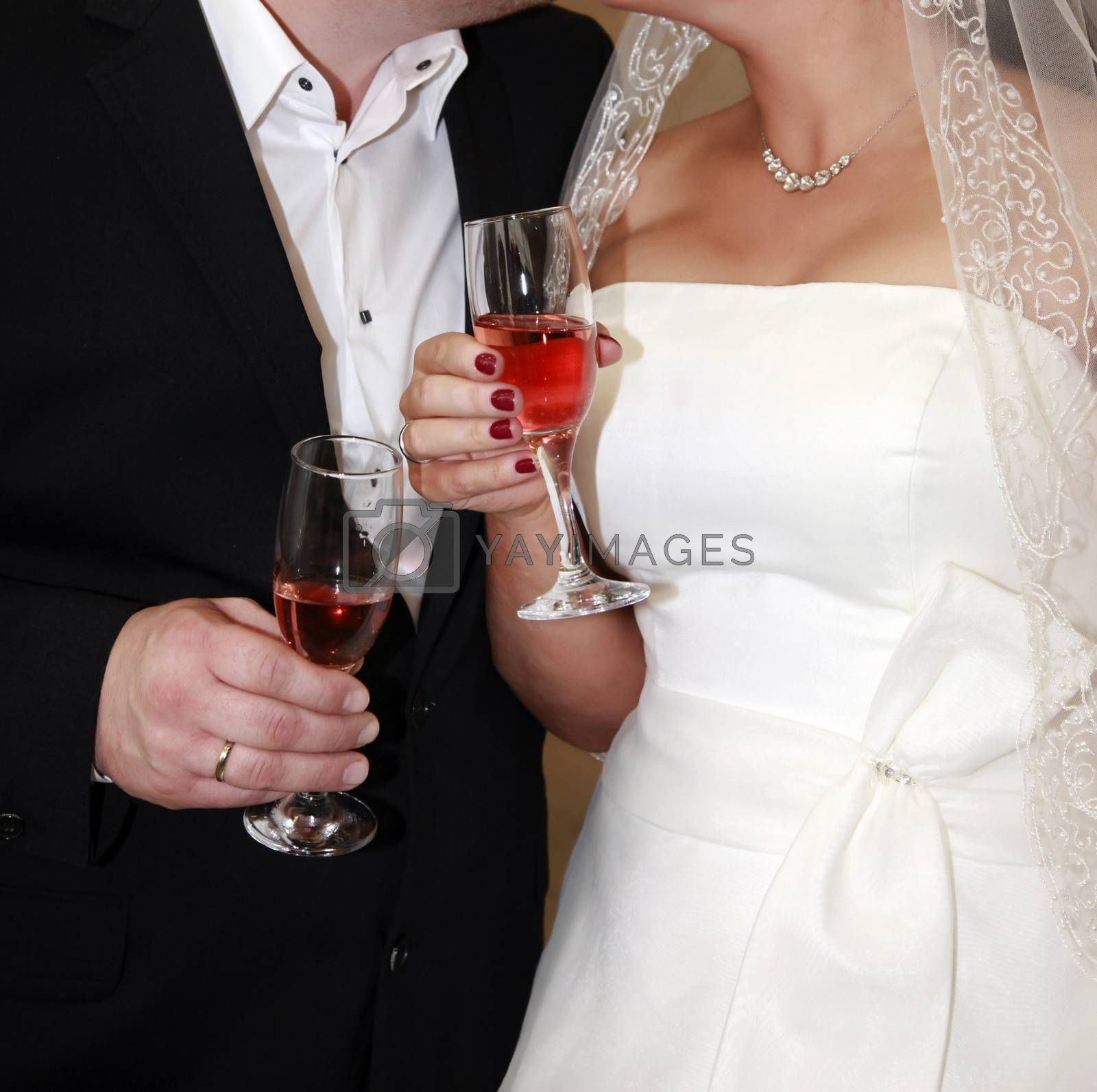 Glasses of champagne in a hand of the groom and bride