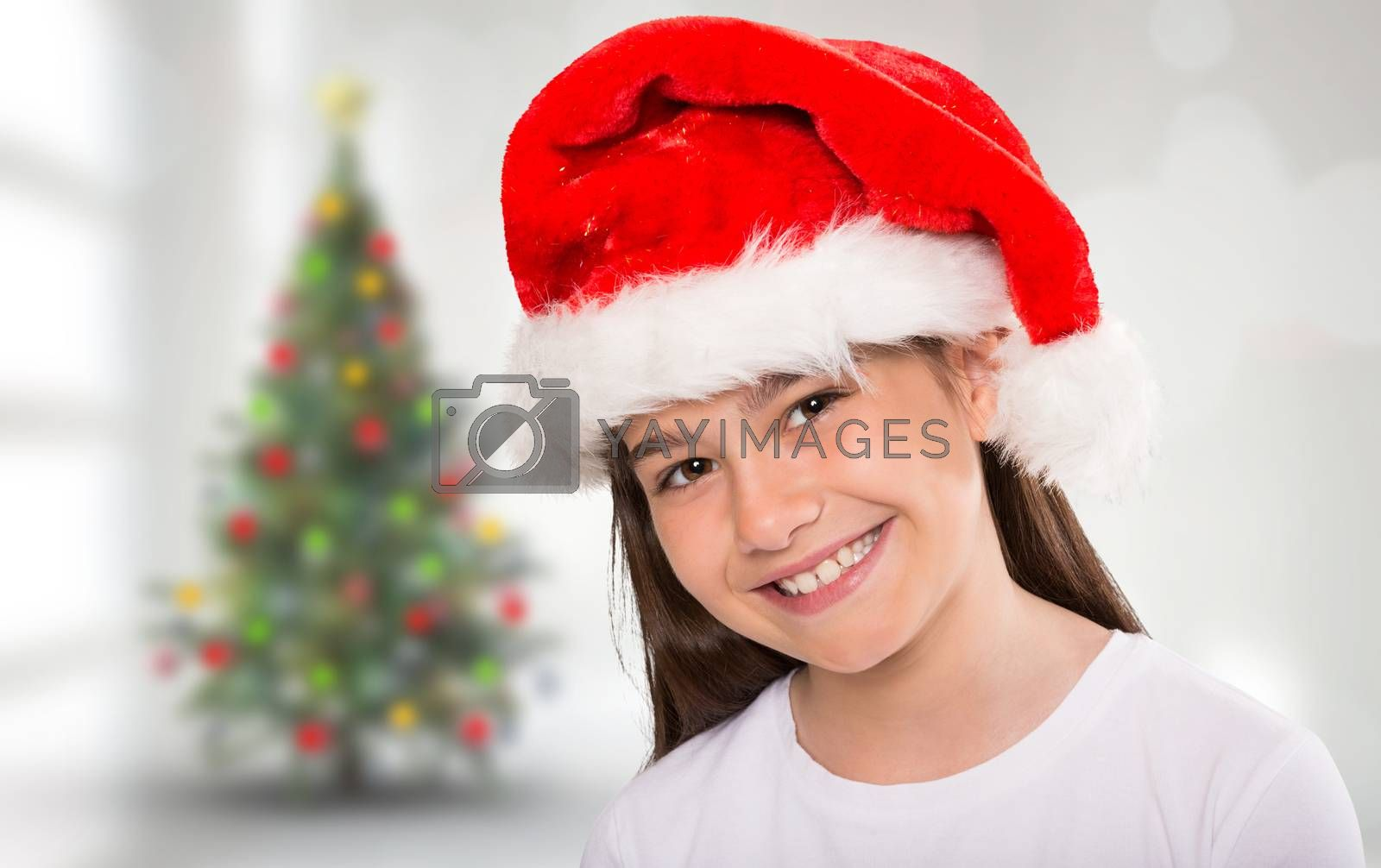 Festive little girl smiling at camera against blurry christmas tree in room