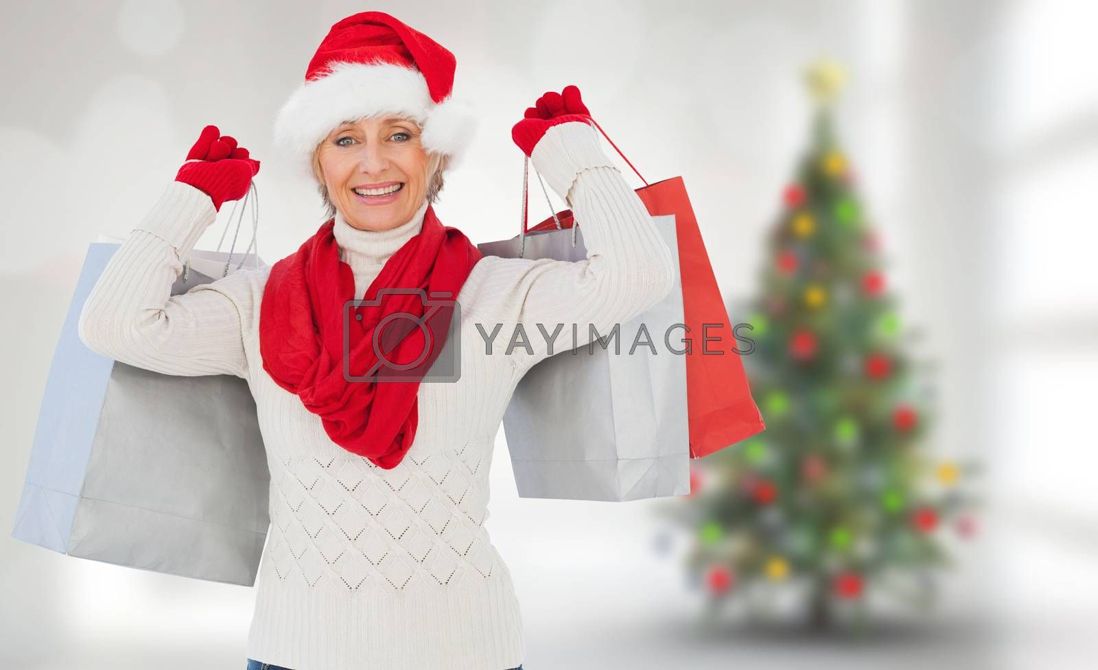 Composite image of festive woman holding shopping bags by Wavebreakmedia