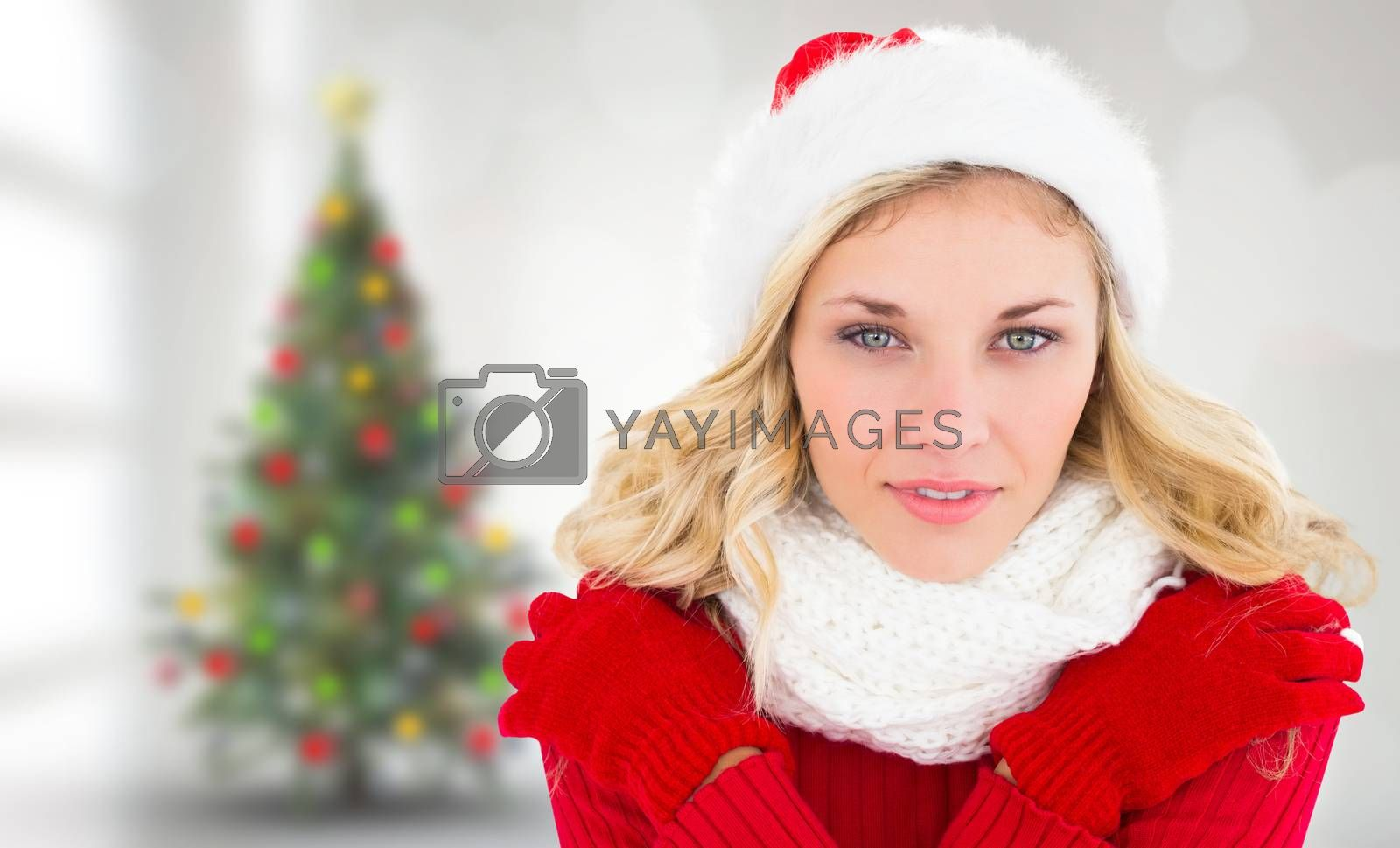 Happy festive blonde  against blurry christmas tree in room